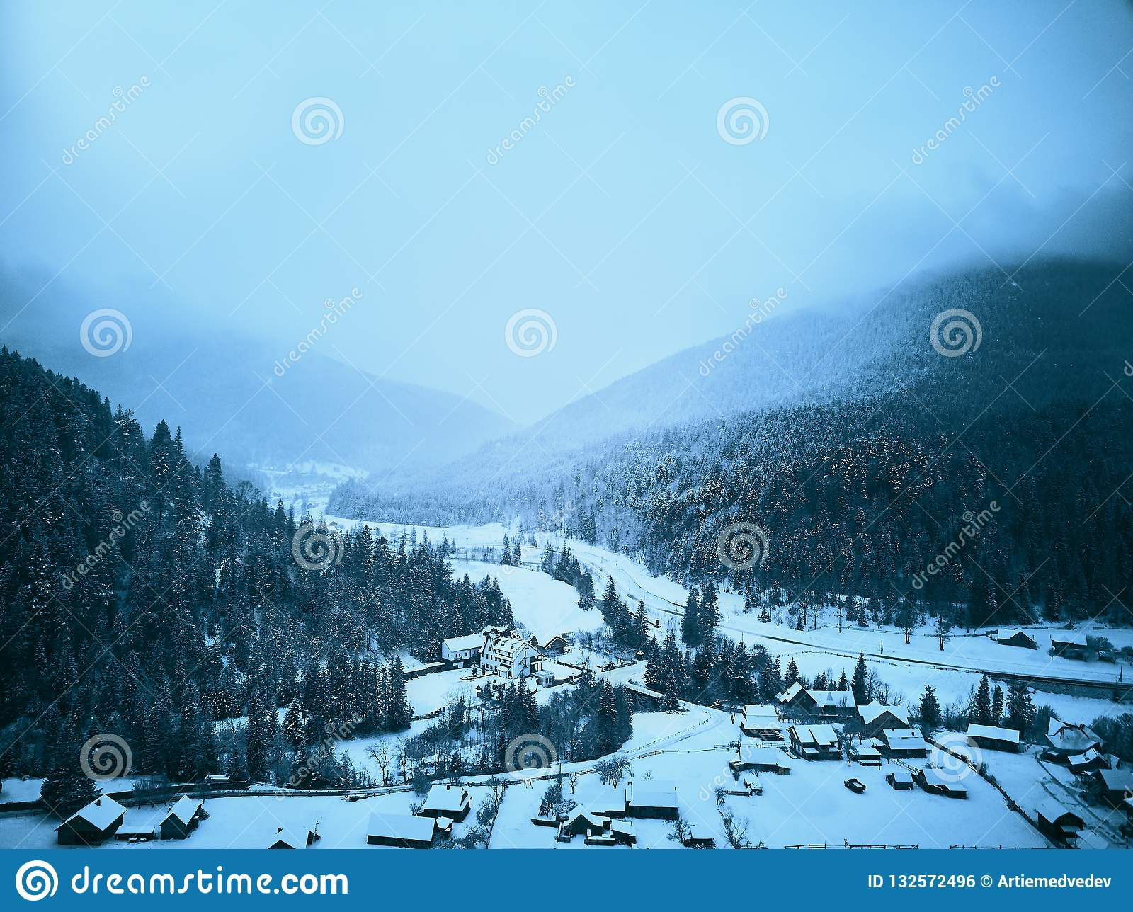 Aerial view of foggy countryside and houses in snowy valley. Hills and mountains with pine tree forest covered in snow