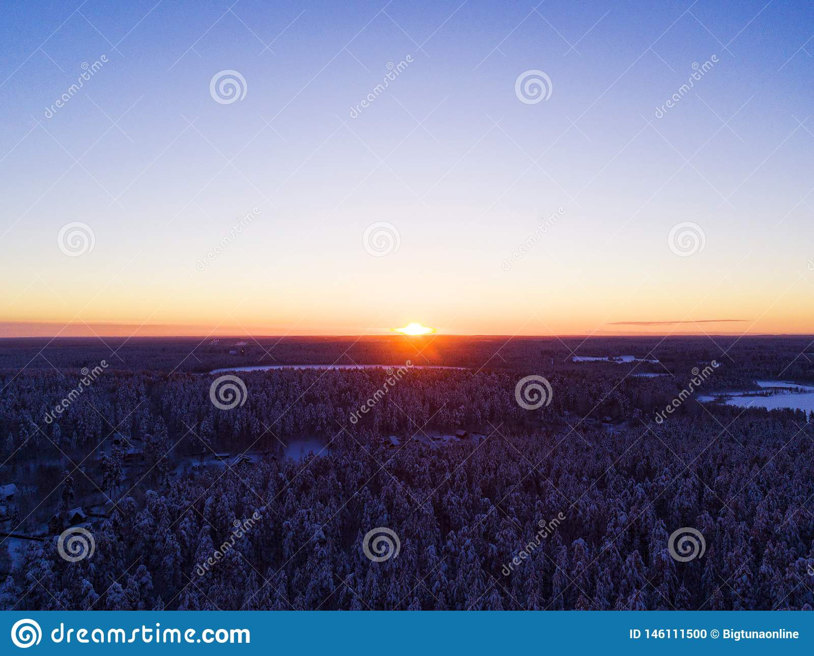 Aerial view of a gold sunset over winter snow-covered pine forest. Winter forest texture. Aerial view. Aerial drone view of a wint