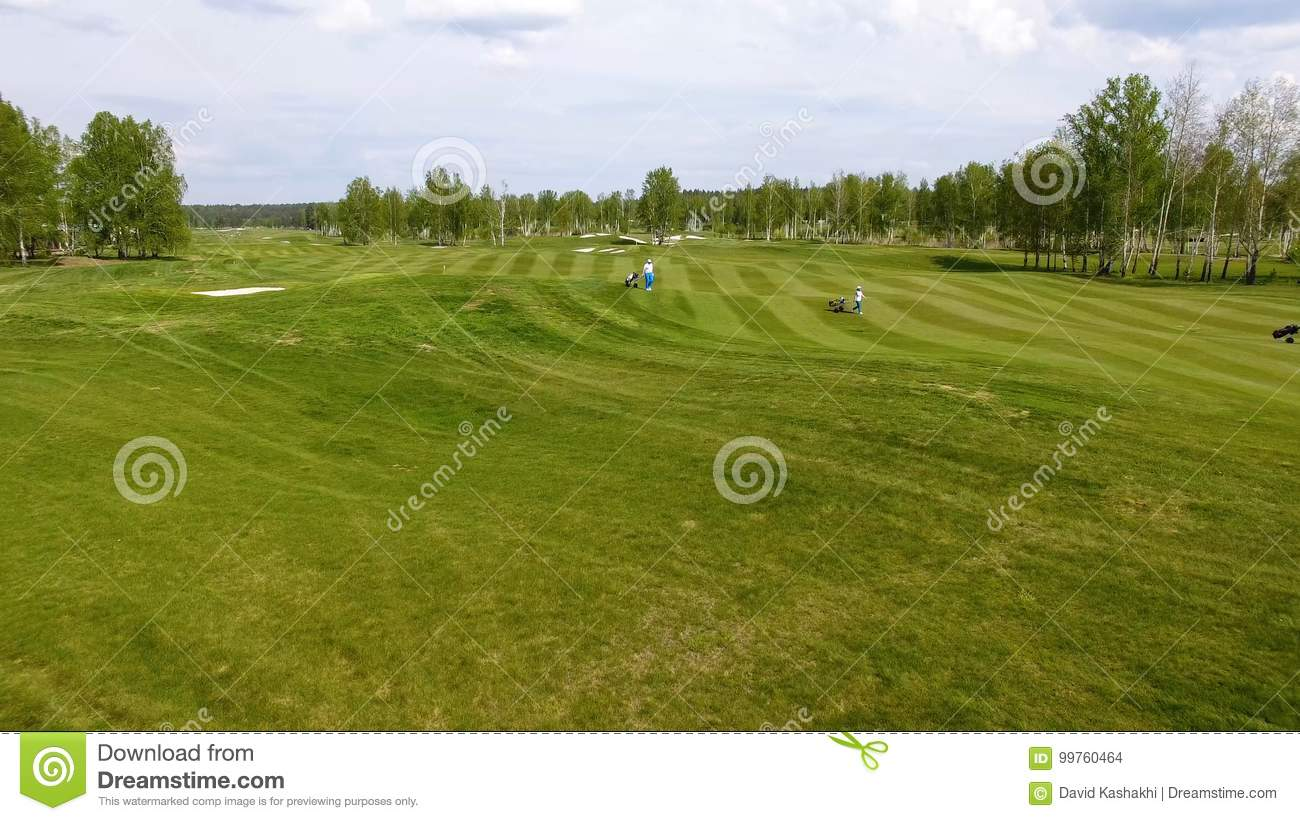 Aerial view Golf course. Golfers walking down the fairway on a course with golf bag and trolley