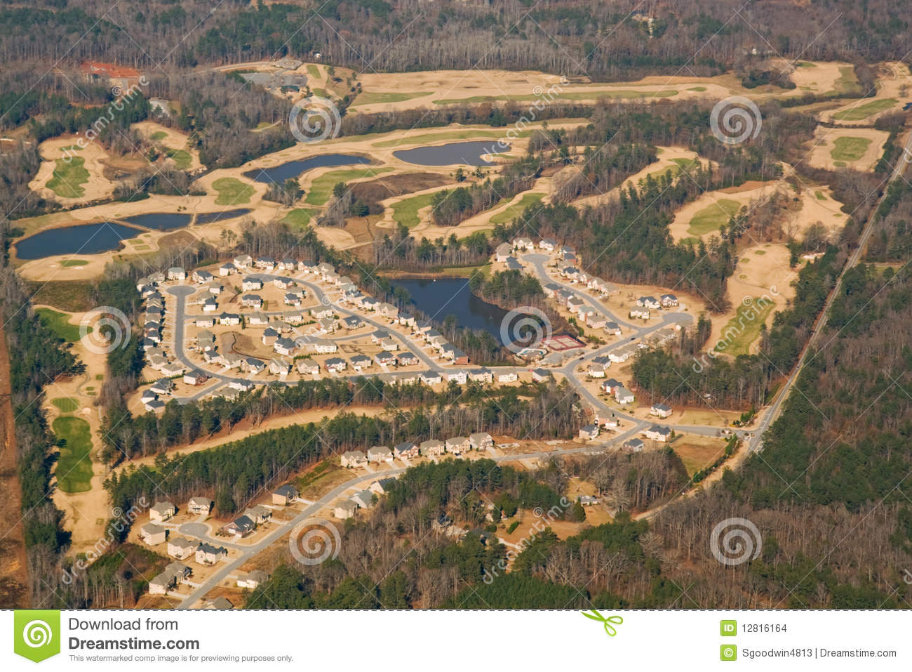Aerial view of a golf course and housing developme