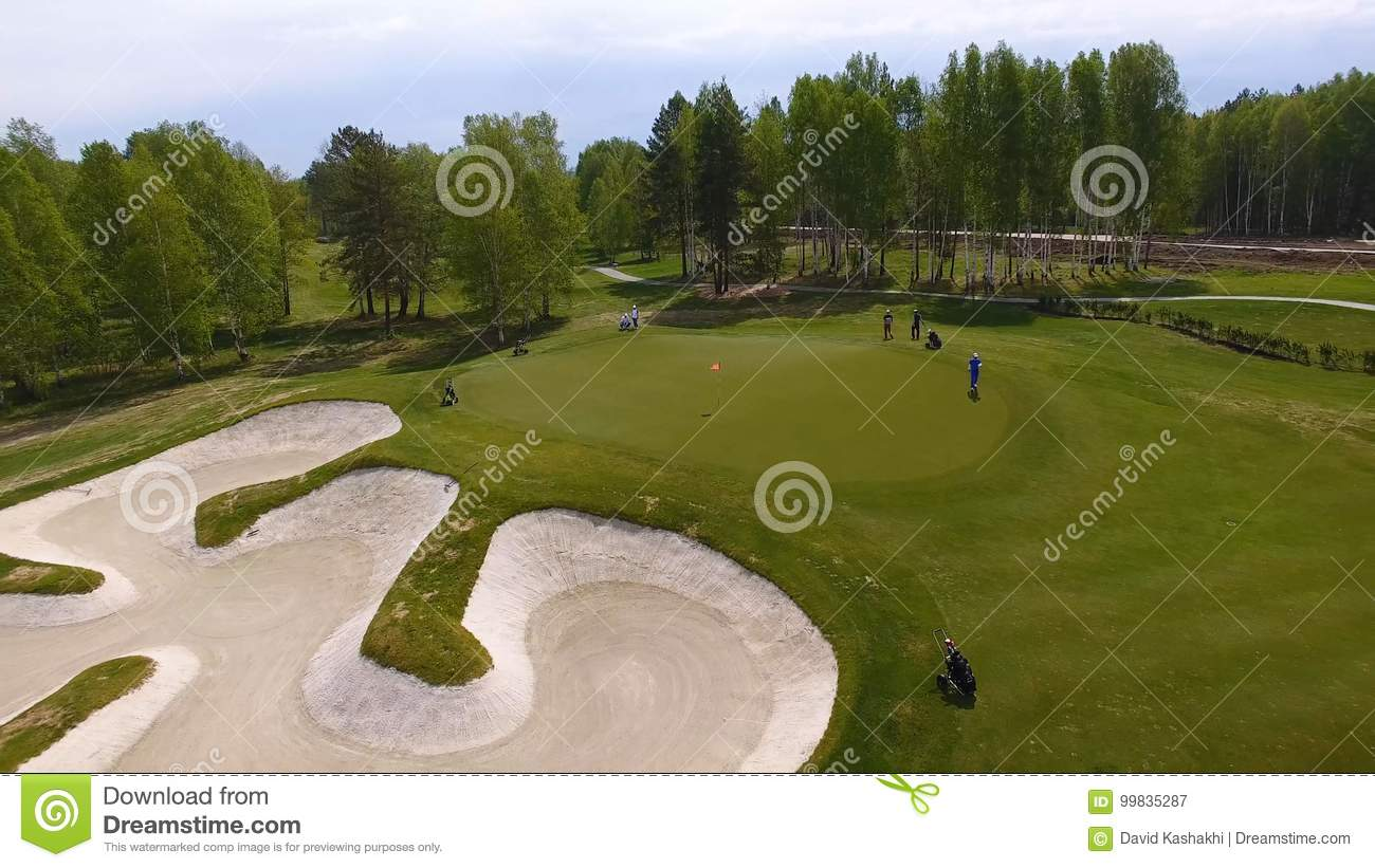 Aerial view of golfers playing on putting green. Professional players on a green golf course