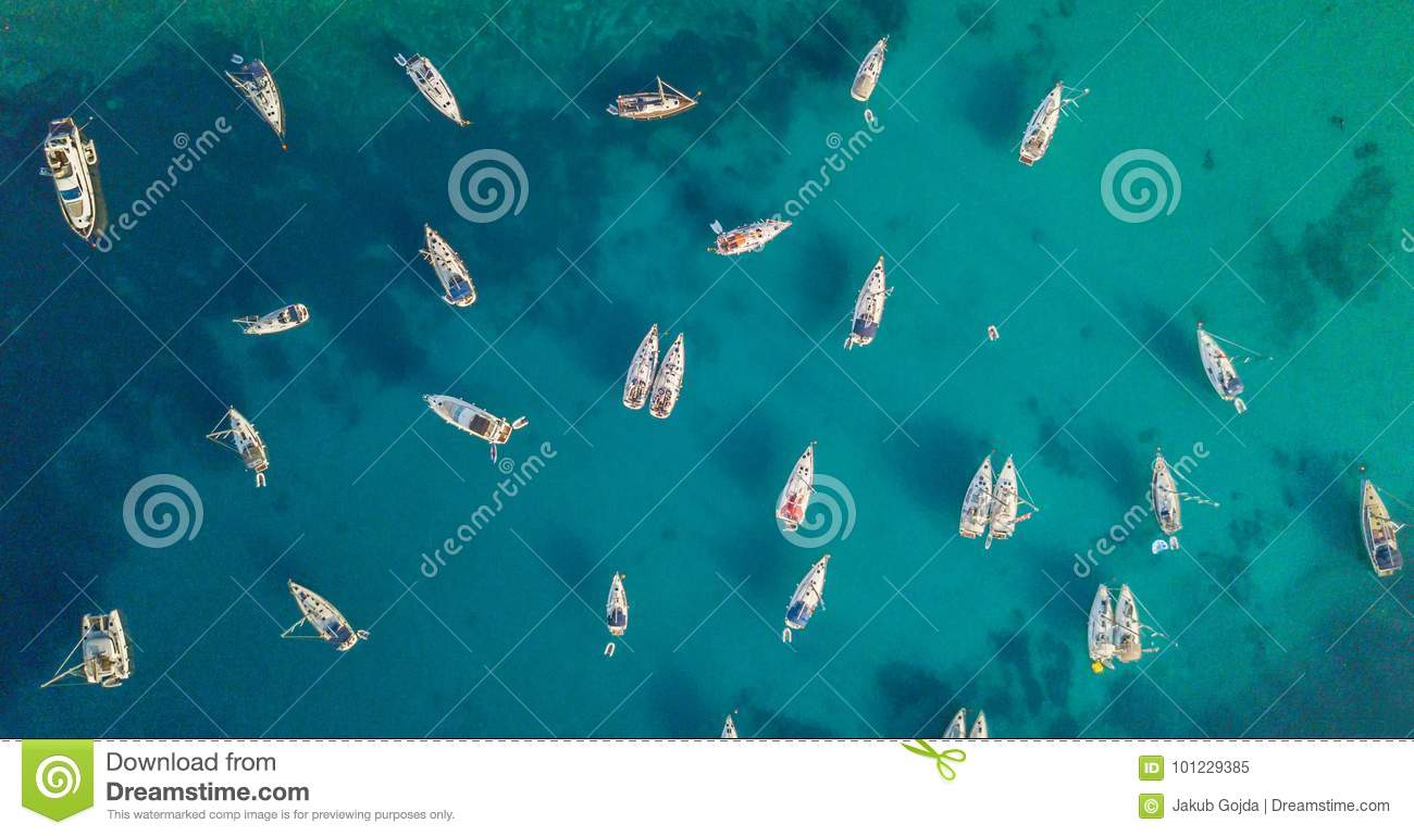 Aerial view of group of sailing boats anchoring on buoys.