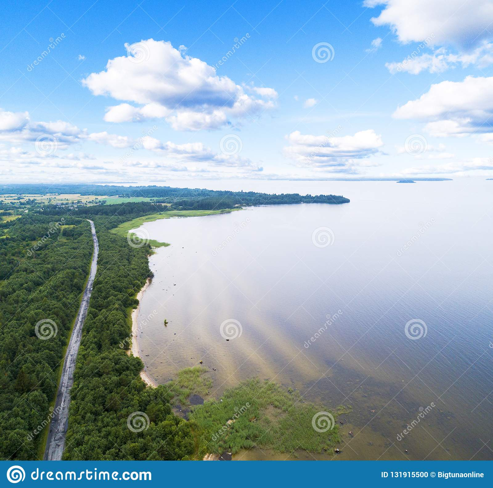 Aerial view of highway. Aerial view of a country road near the lake. Car passing by. Aerial road. Aerial view flying. Captured fro