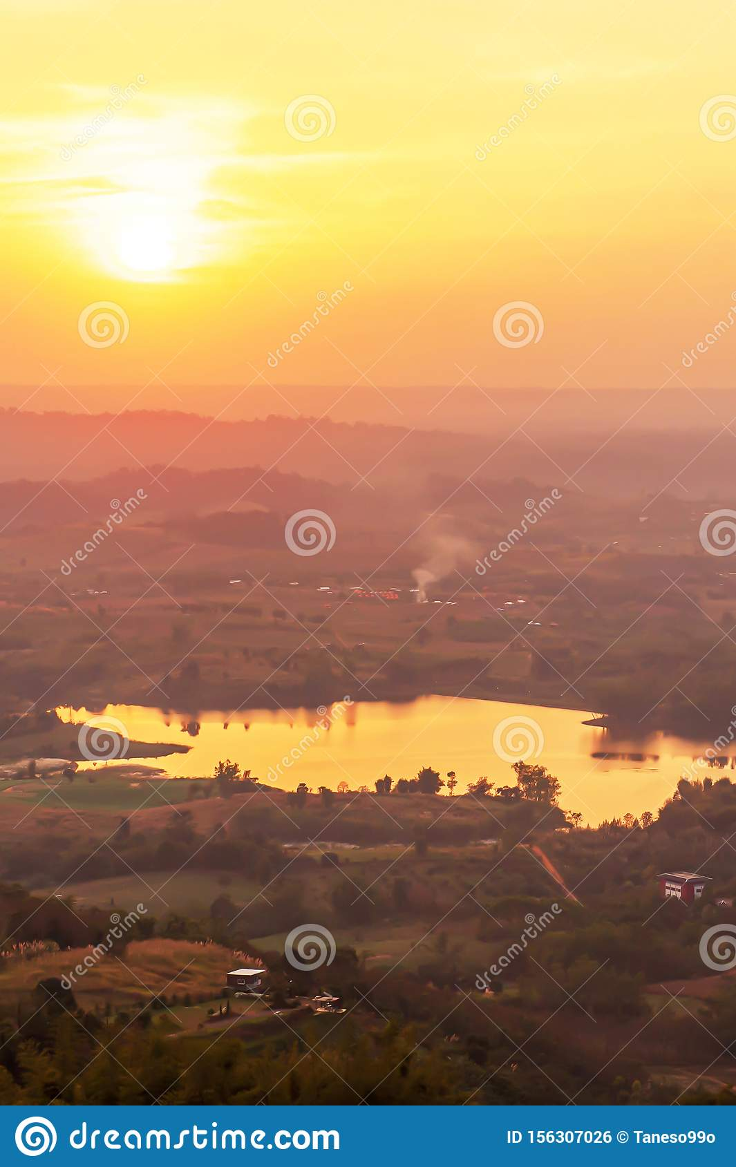 Aerial view of lake with the sun setting over a mountain range