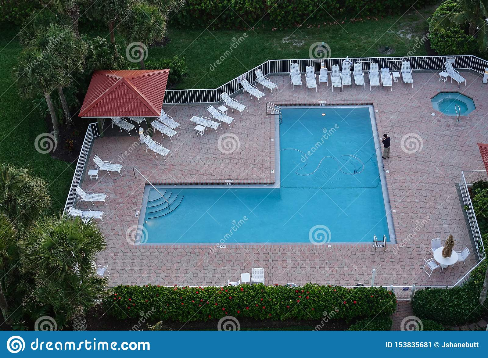 Aerial view of a man cleaning a resort pool