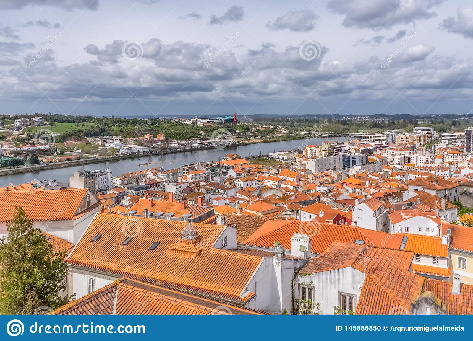 Aerial view on Mondego river and banks with Coimbra city, sky with clouds as background, in Portugal