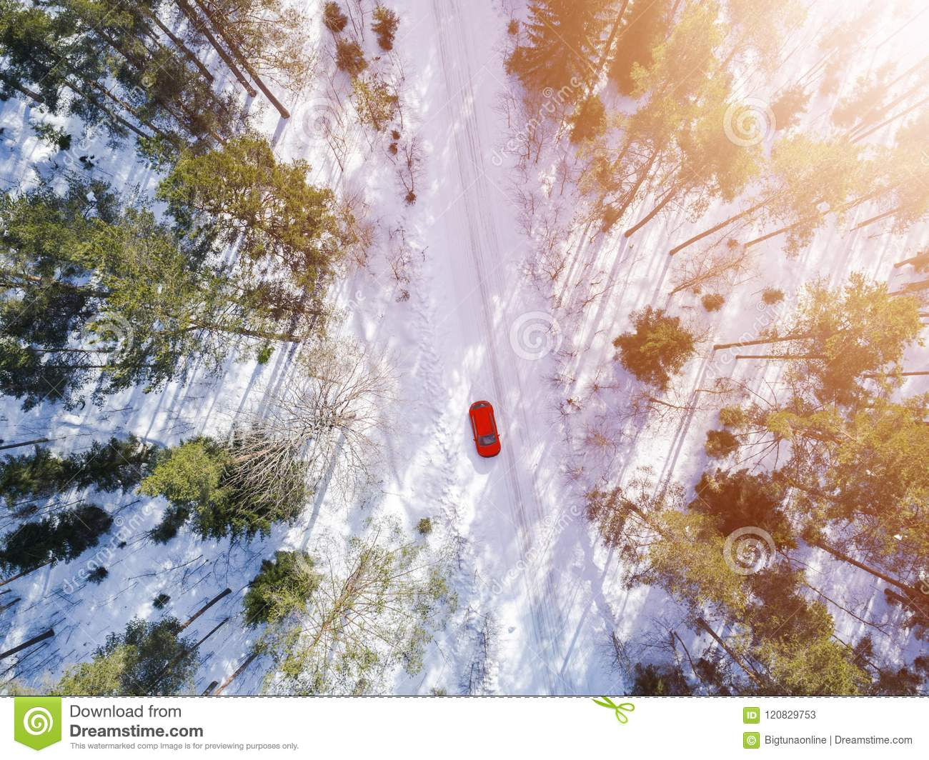 Aerial view of a red car on white winter road. Winter landscape countryside. Aerial photography of snowy forest with a red car on