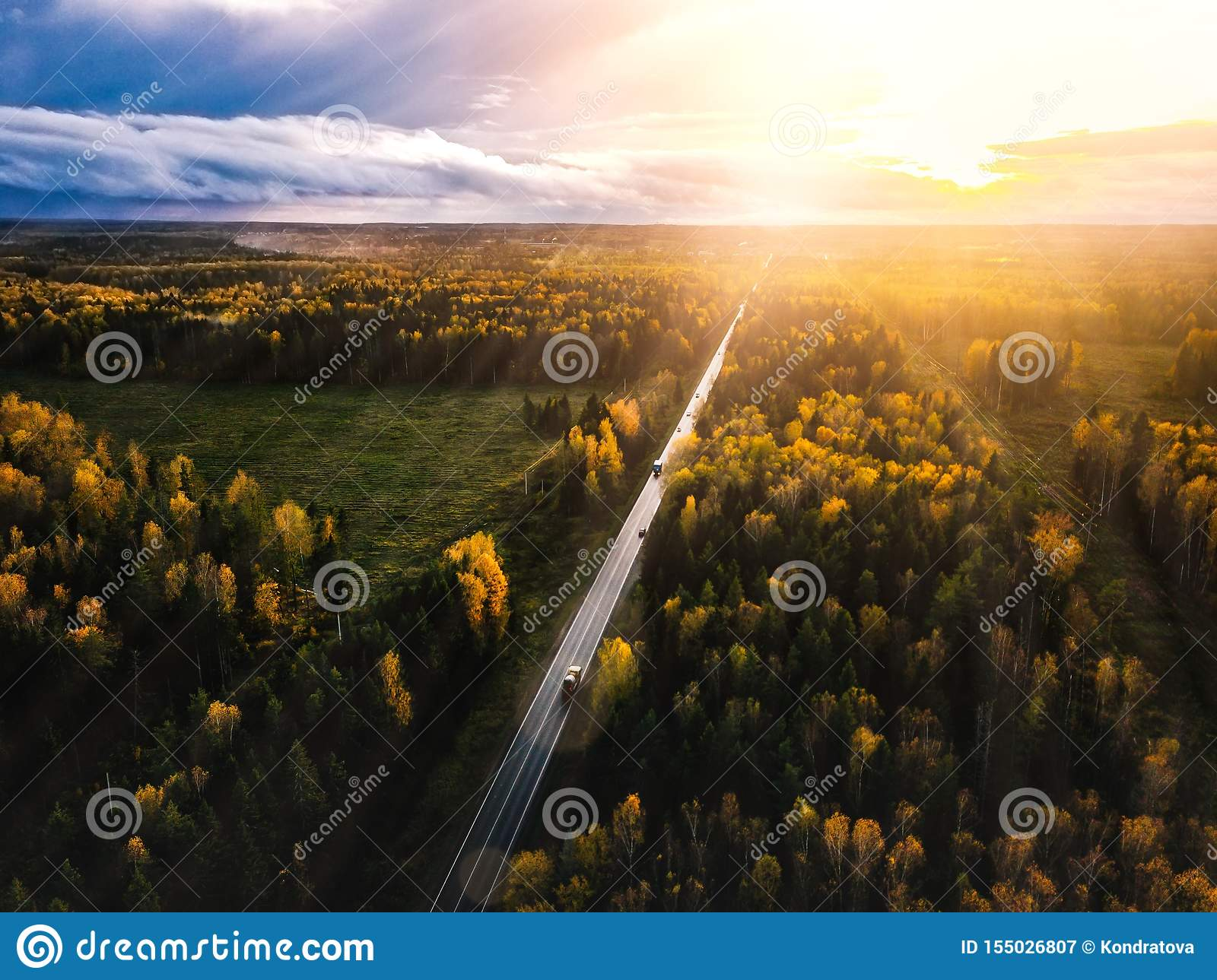 Aerial view of road in beautiful autumn forest at sunset in rural Finland