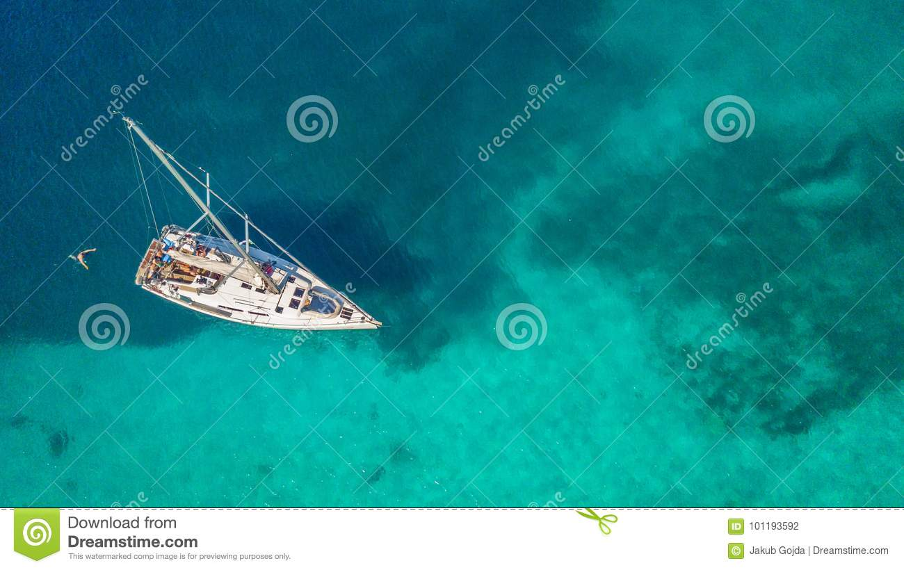 Aerial view of sailing boat anchoring on coral reef