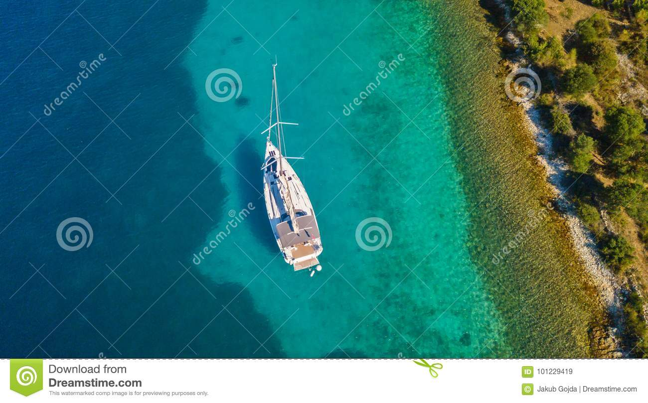 Aerial view of sailing boat anchoring next to reef