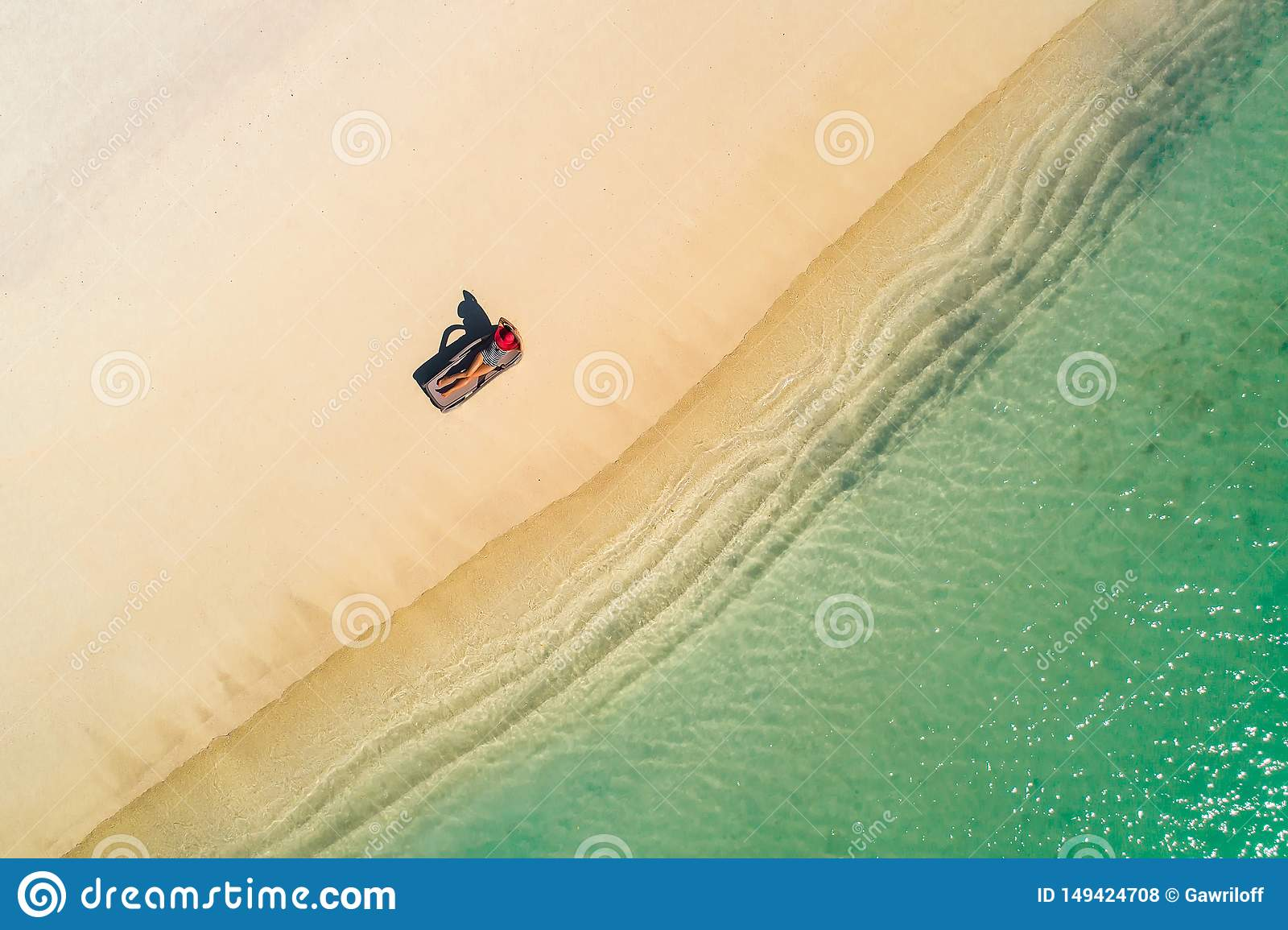Aerial view of slim woman sunbathing lying on a beach chairin Seychelles. Summer seascape with girl, beautiful waves, colorful