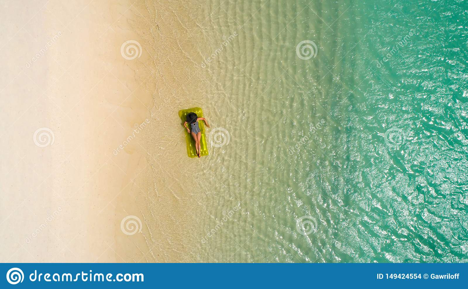 Aerial view of slim woman swimming on the swim mattress in the transparent turquoise sea in Seychelles. Summer seascape with girl