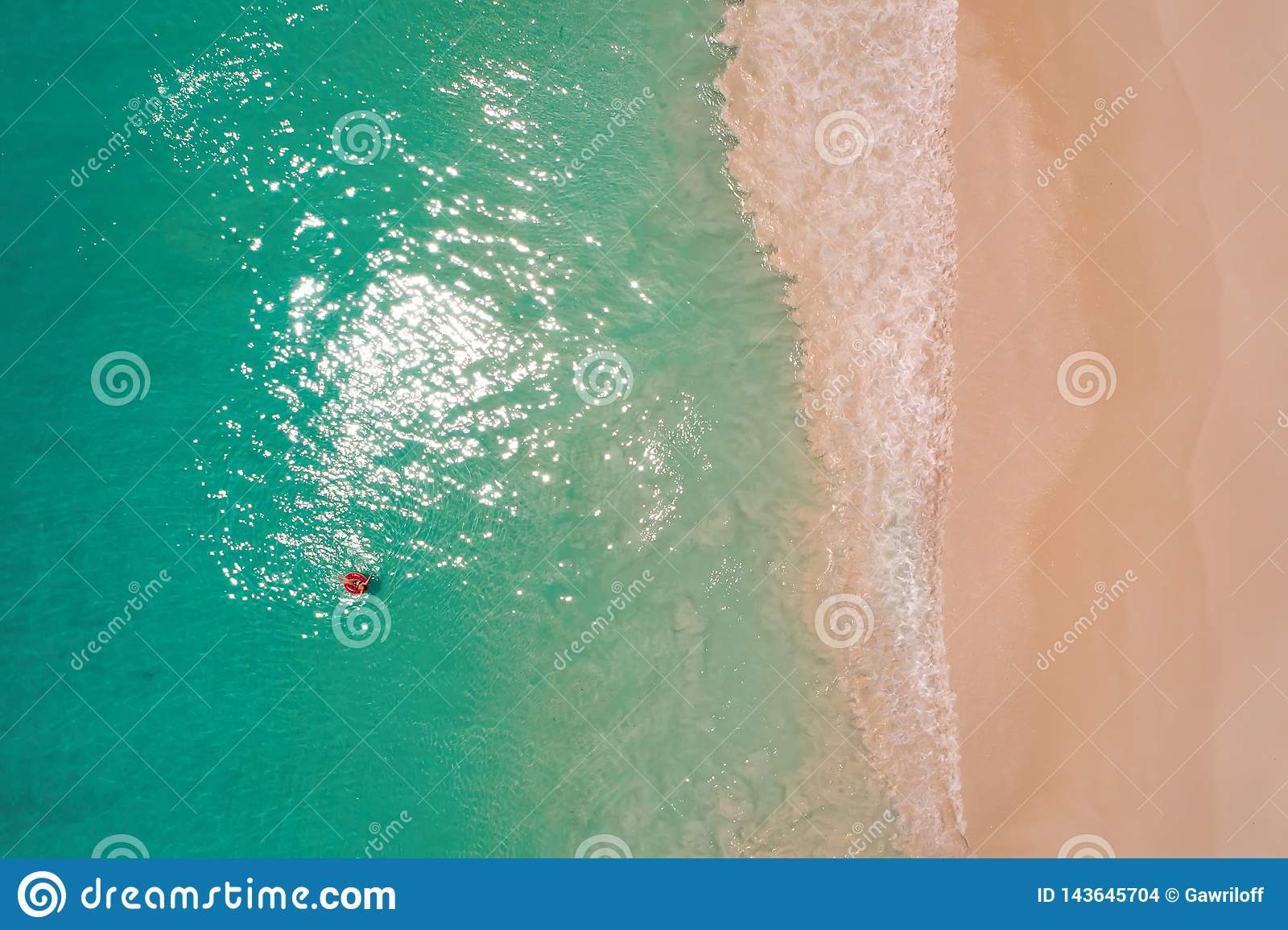 Aerial view of slim woman swimming on the swim ring  donut in the transparent turquoise sea in Seychelles. Summer seascape with