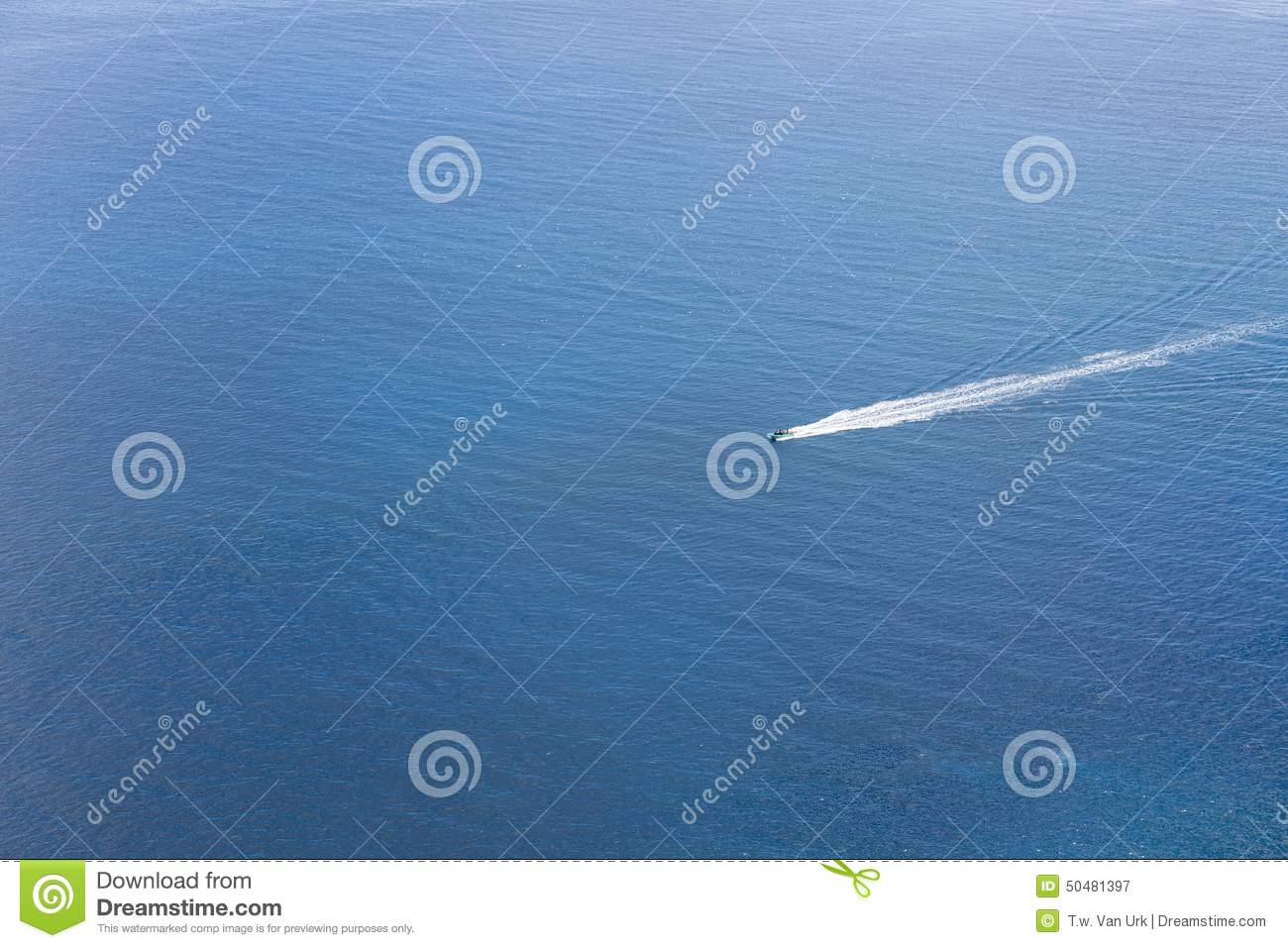 Aerial view of a small ship navigating at a blue ocean
