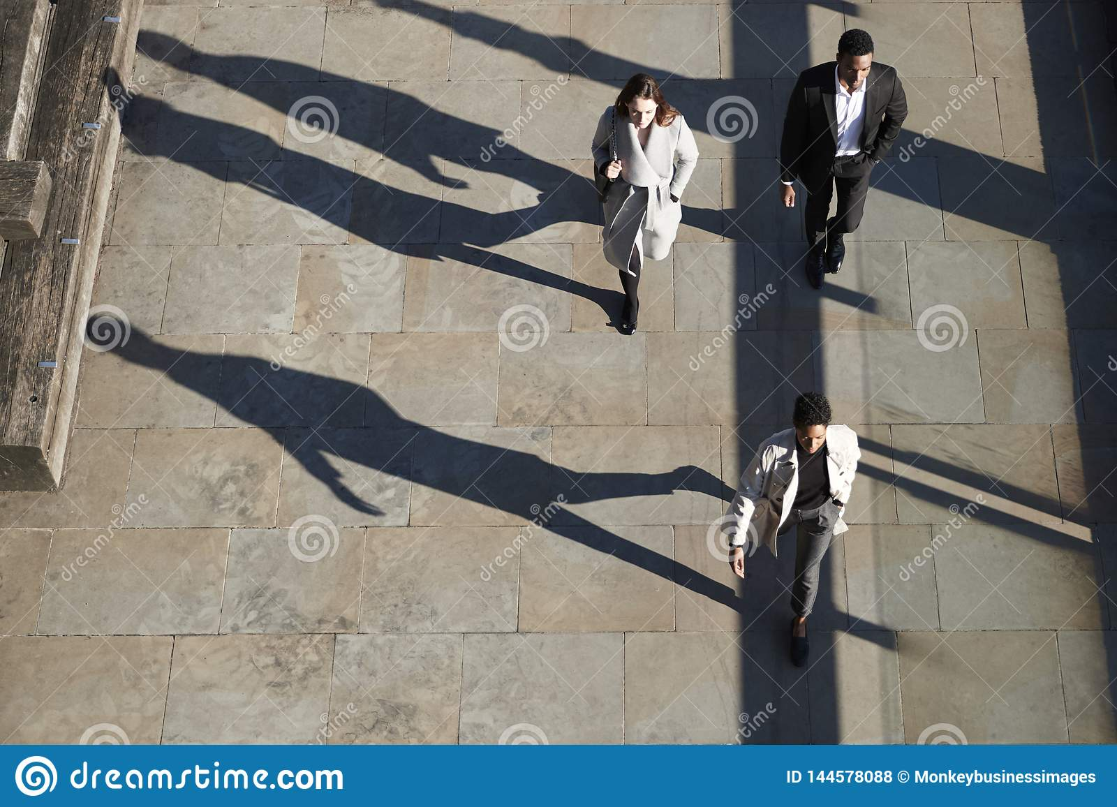 Aerial view of three city workers walking on a sunny urban street, horizontal