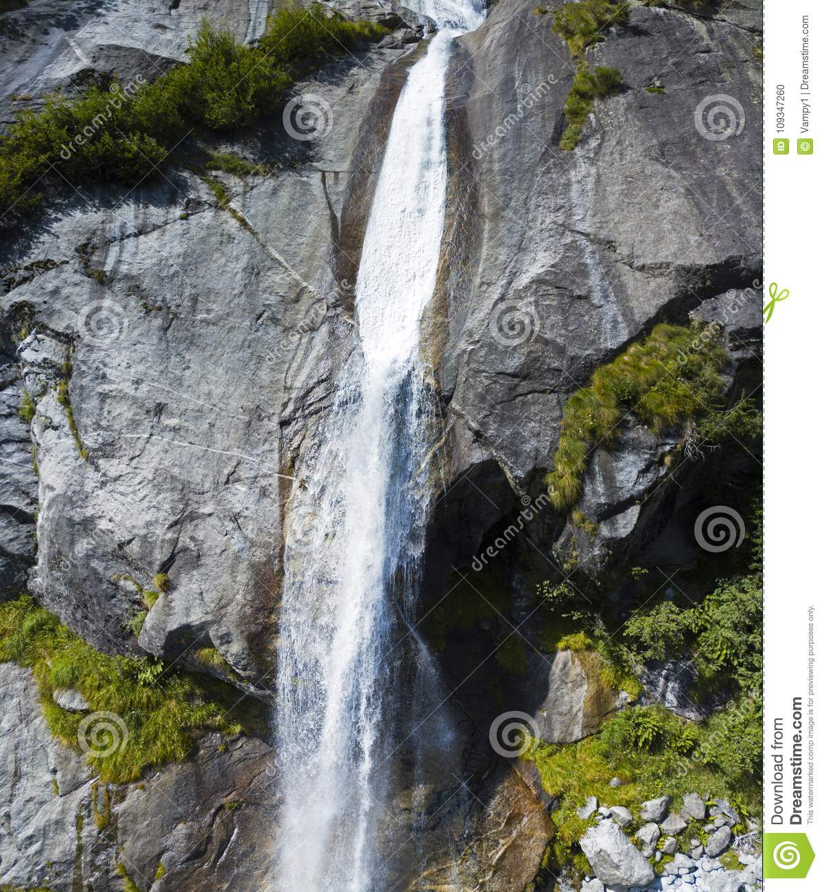 Aerial view of a waterfall in Val di Mello, a green valley surrounded by granite mountains and forest trees. Val Masino. Italy