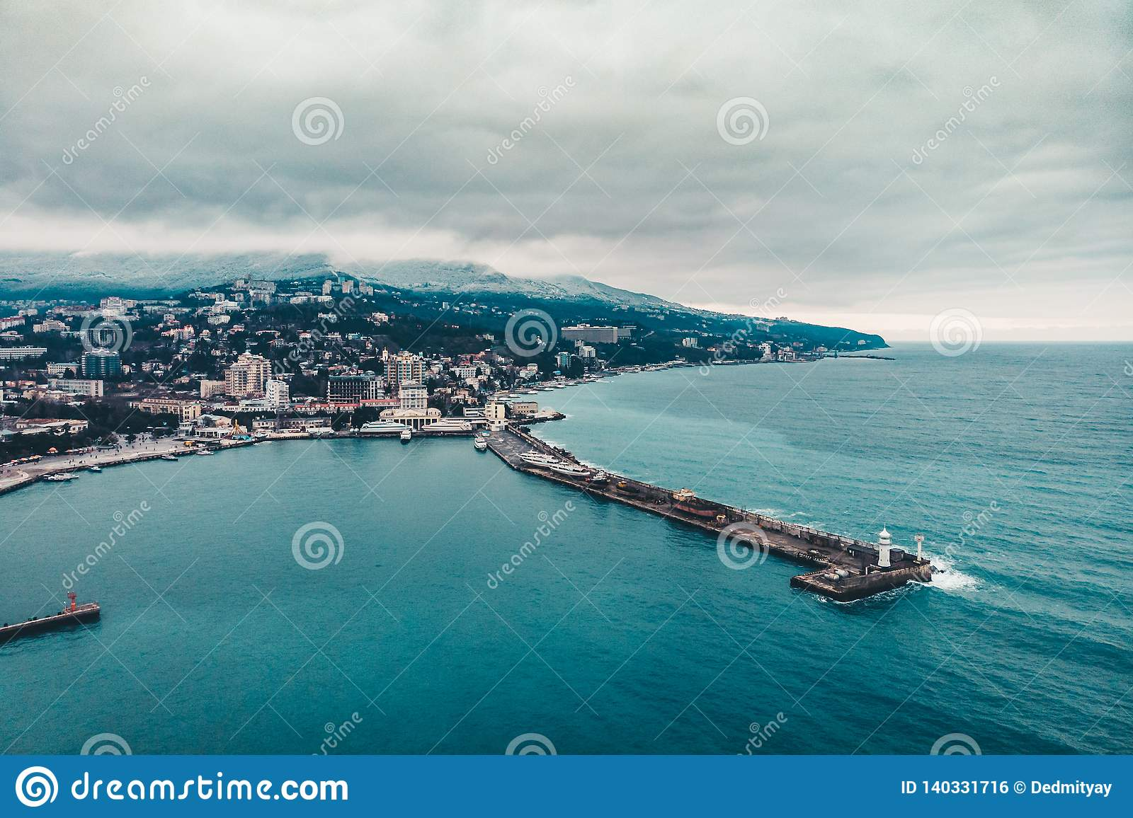 Aerial view of Yalta embankment from drone, old Lighthouse on pier, sea coast landscape and city buildings on mountains, Crimea