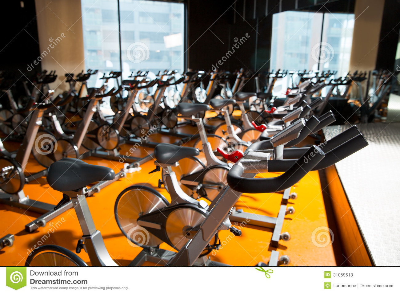 Aerobics spinning exercise bikes gym room in a row royalty