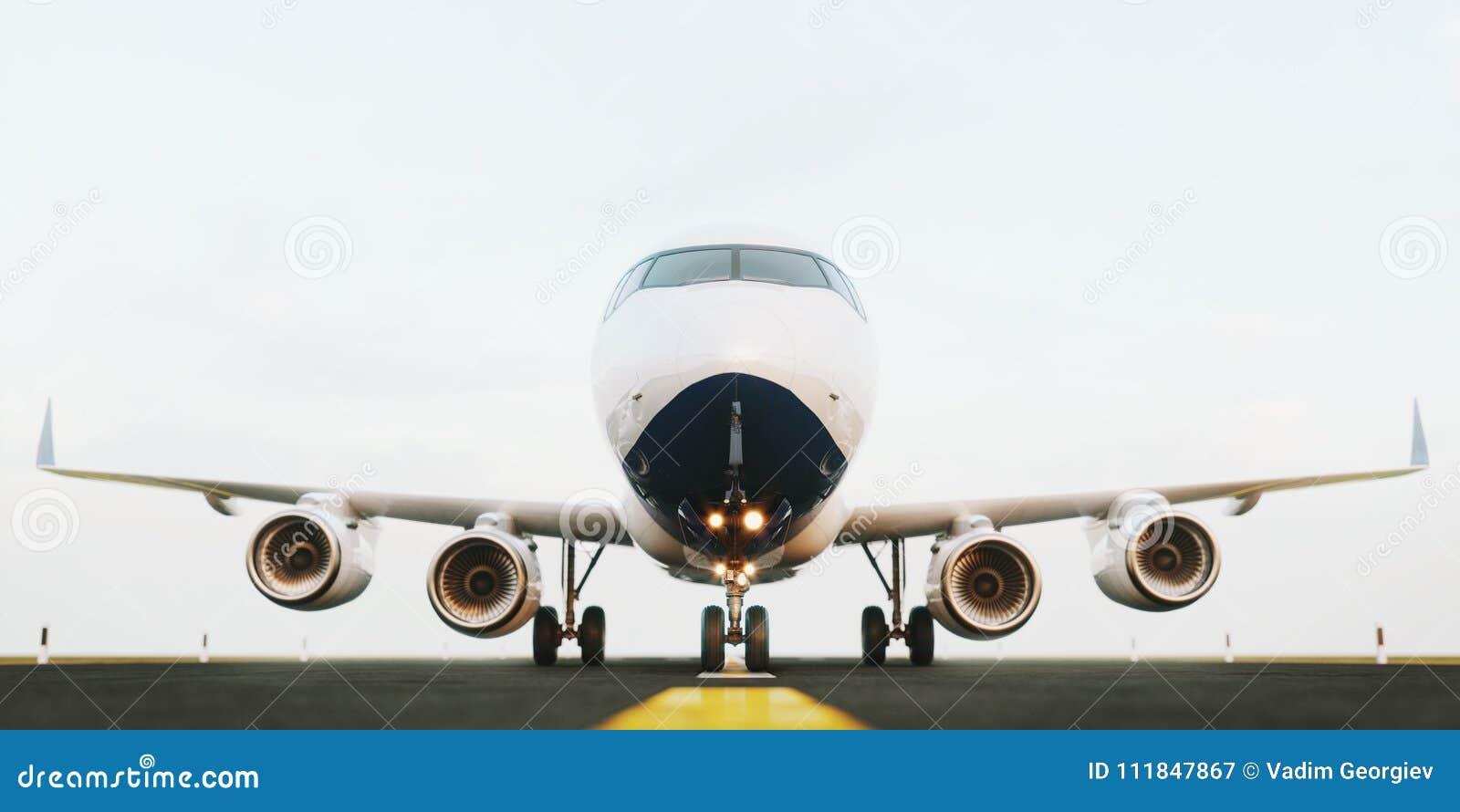 Aeroplano comercial blanco que se coloca en la pista del aeropuerto en la puesta del sol La vista delantera del aeroplano del pas
