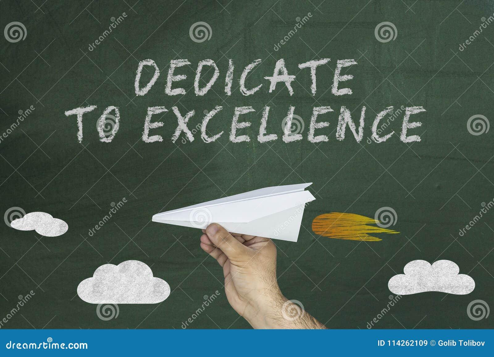 Aeroplano de papel y texto en la pizarra: Dedicado a la excelencia