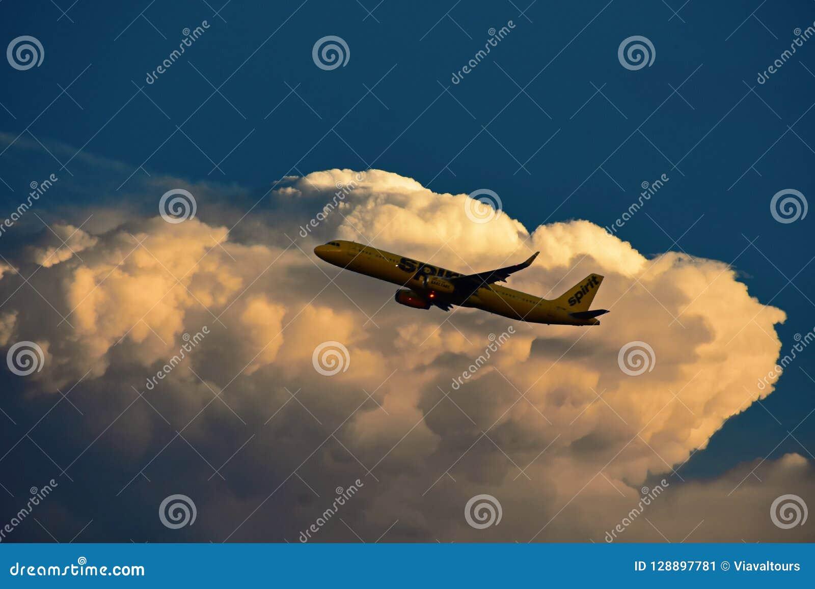 Aeroplano de Spirit Airlines que gana altitud después de despegue, en el cielo hermoso de la puesta del sol