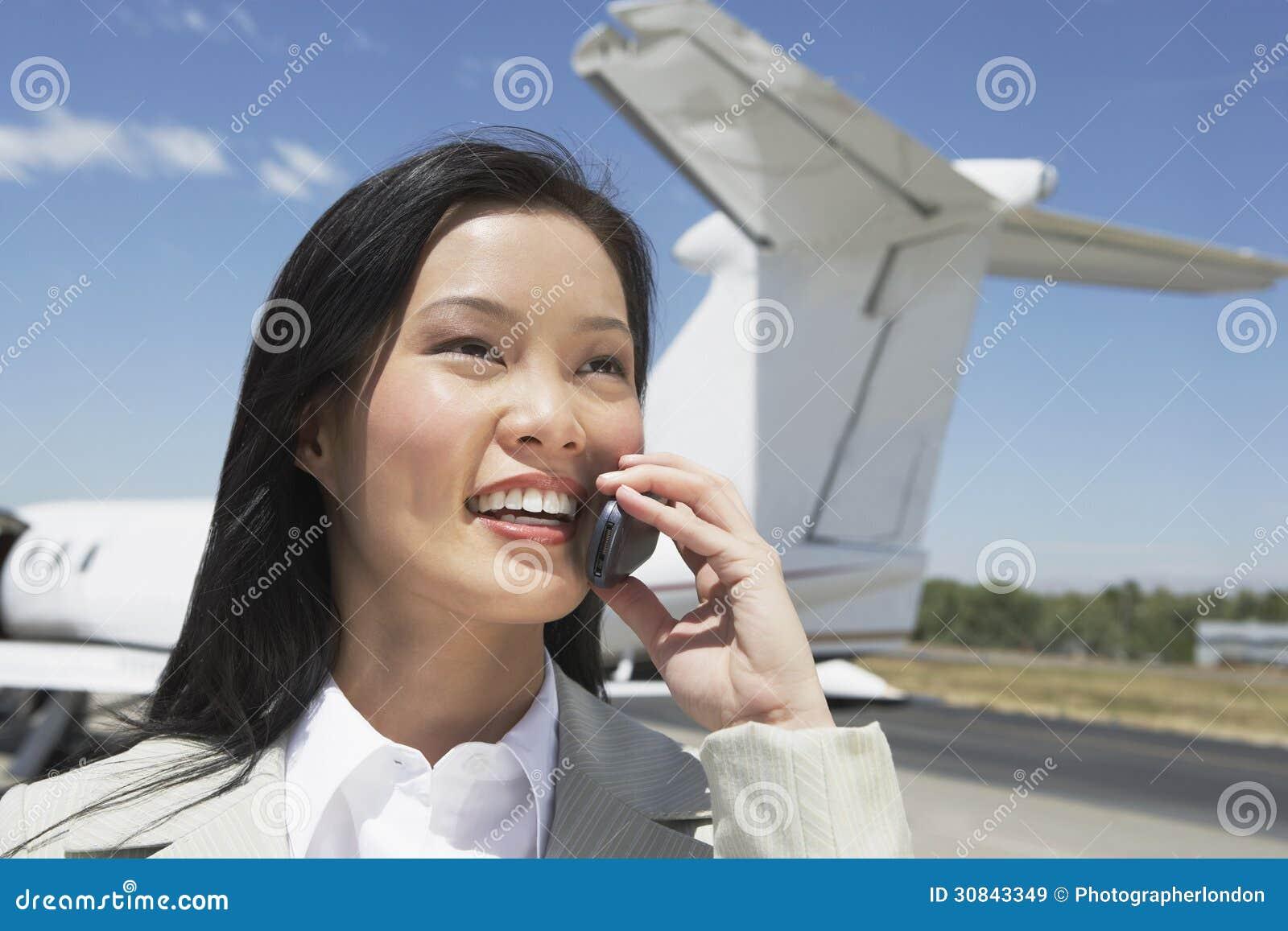 Aeroplano de Using Cellphone With de la empresaria en fondo