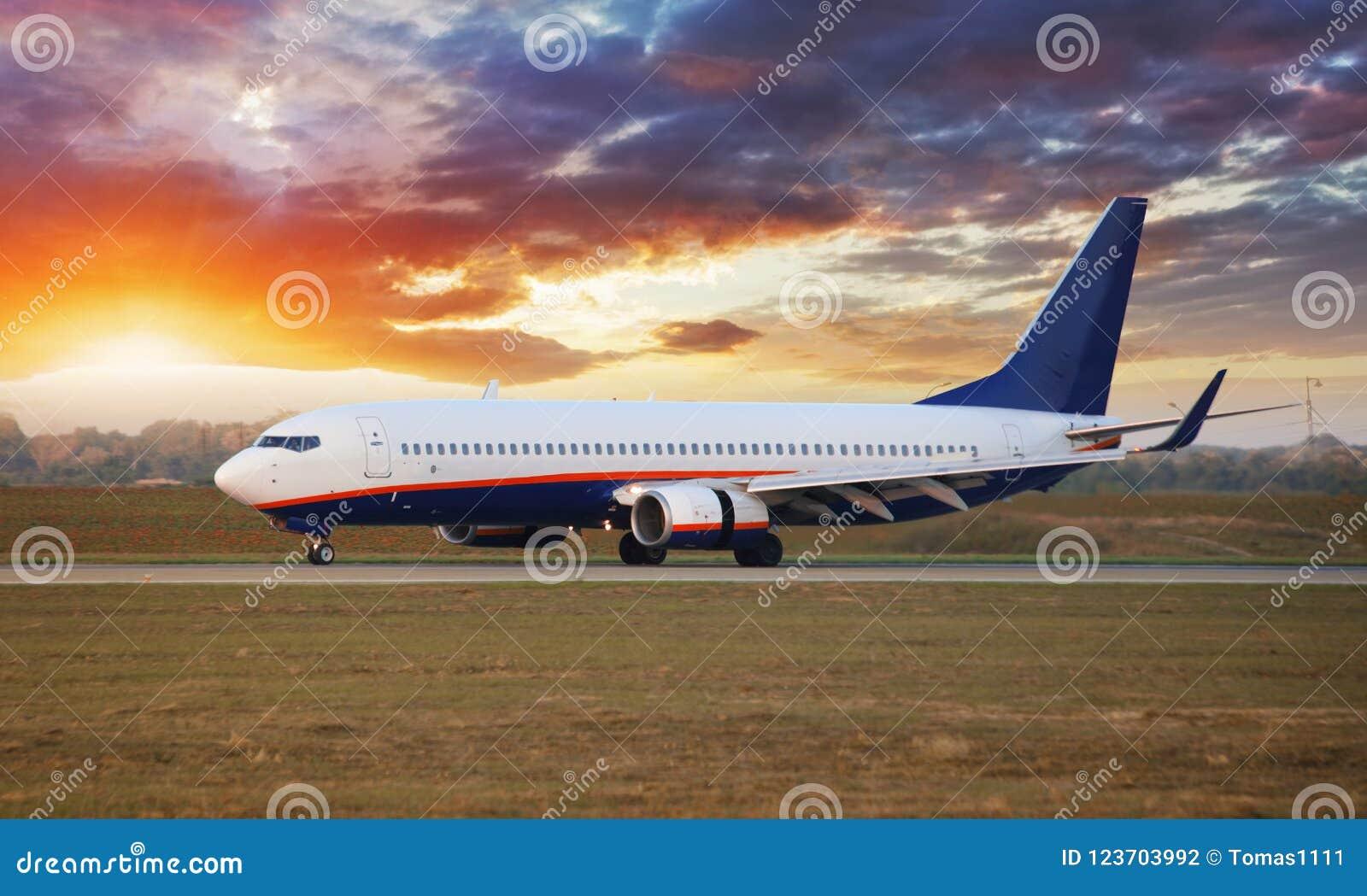 Aeroplano del aterrizaje en aeropuerto en la puesta del sol