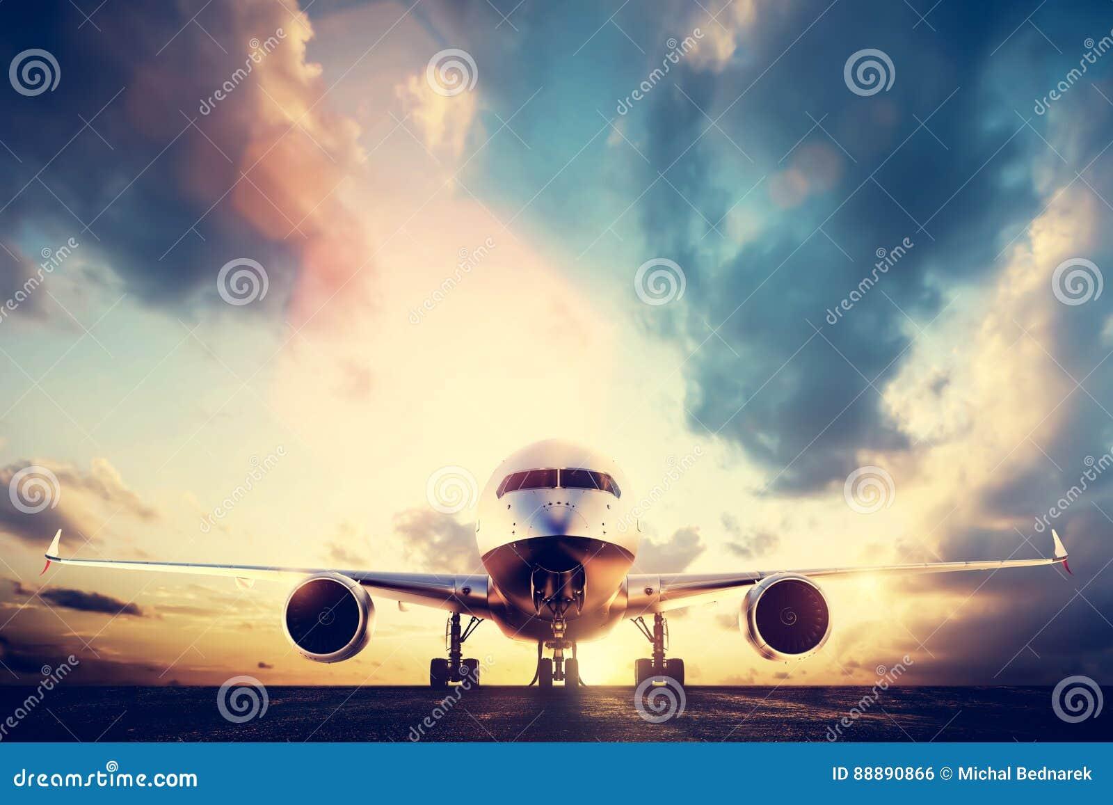 Aeroplano del passeggero che decolla sulla pista al tramonto