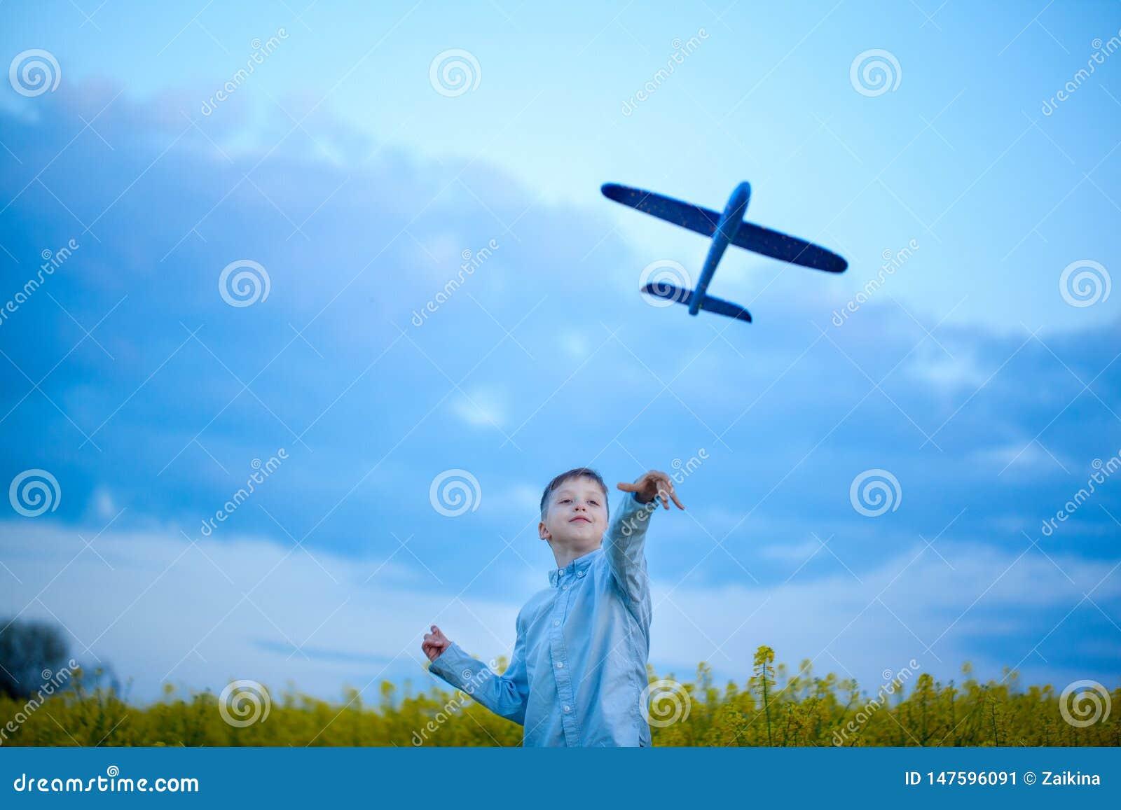 Aeroplano di lancio del giocattolo del ragazzo nel giorno di estate