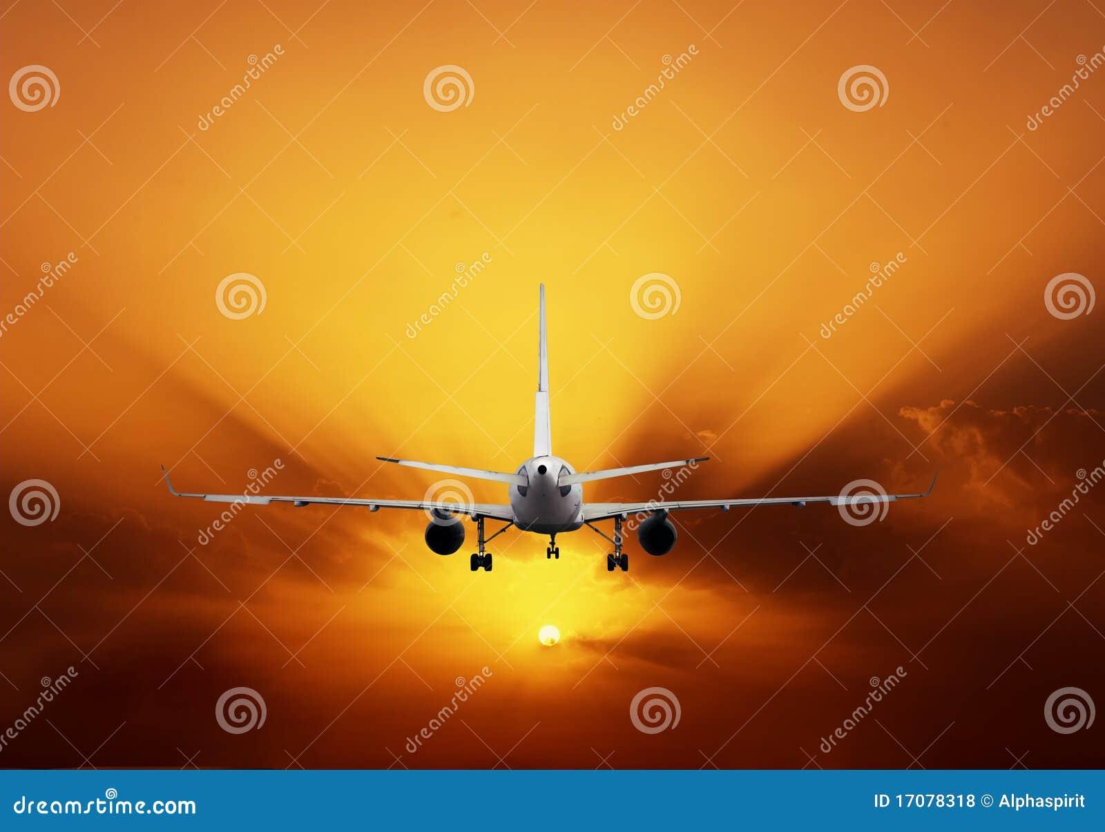 Aeroplano en el cielo de la puesta del sol