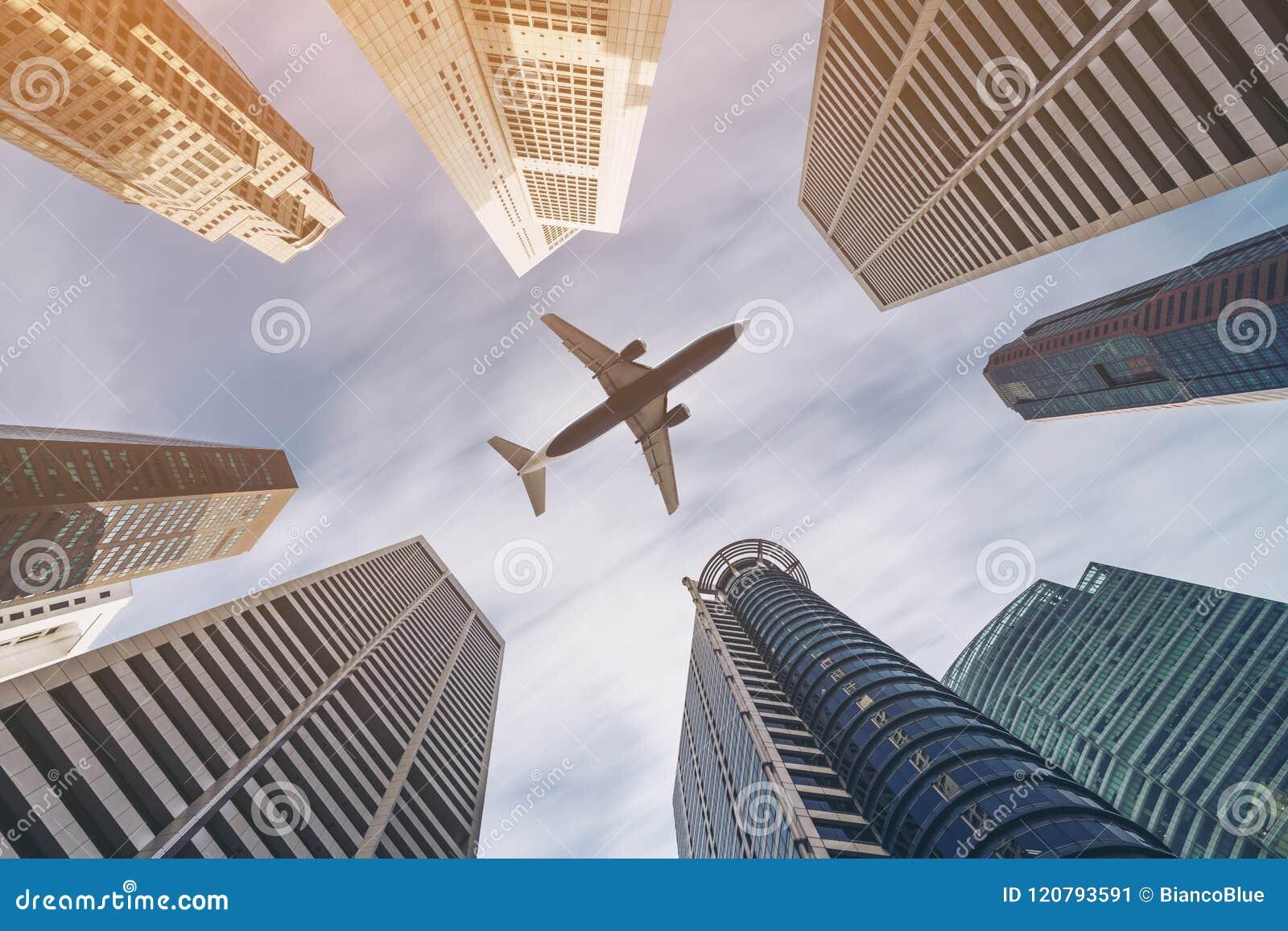 Aeroplano que vuela sobre edificios del negocio de la ciudad, skyscrap de gran altura