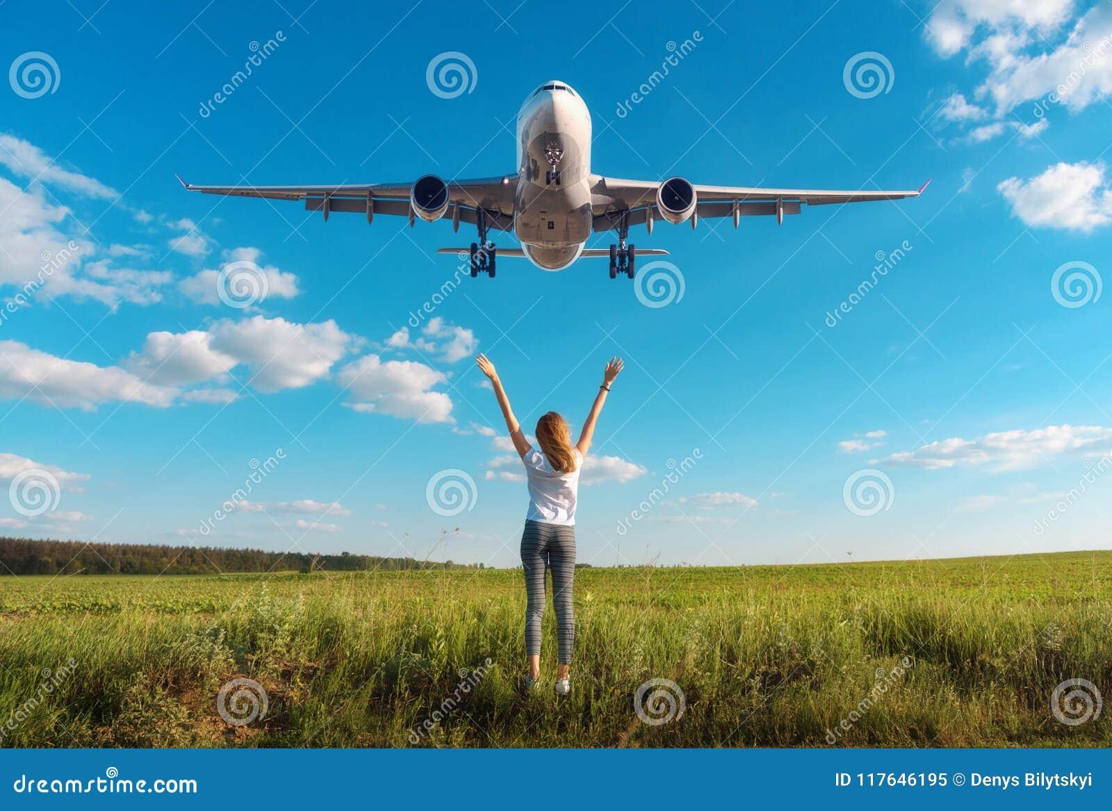 Aeroplano y mujer en el campo en la puesta del sol en verano