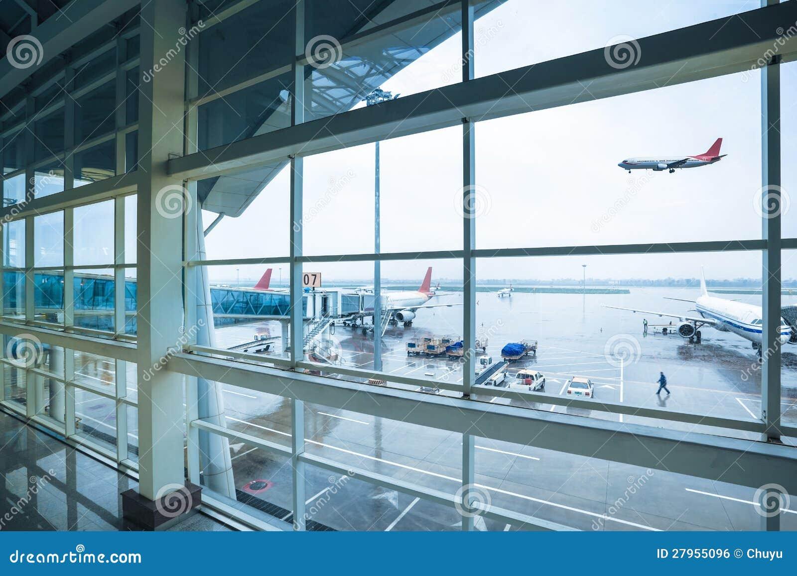 Aeroporto fuori della finestra in pioggia