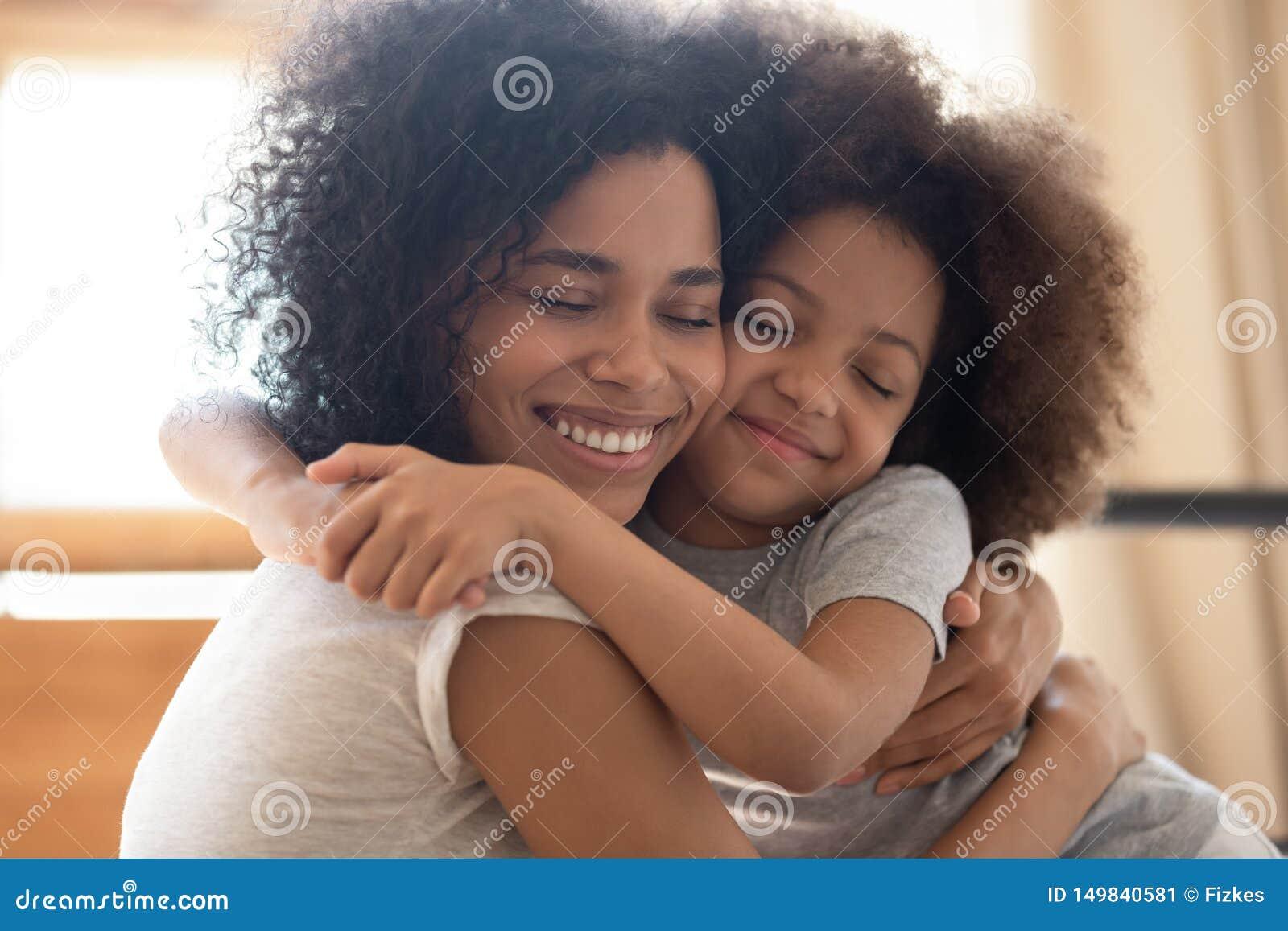 Afago africano afetuoso bonito do abraço da filha da mãe e da criança