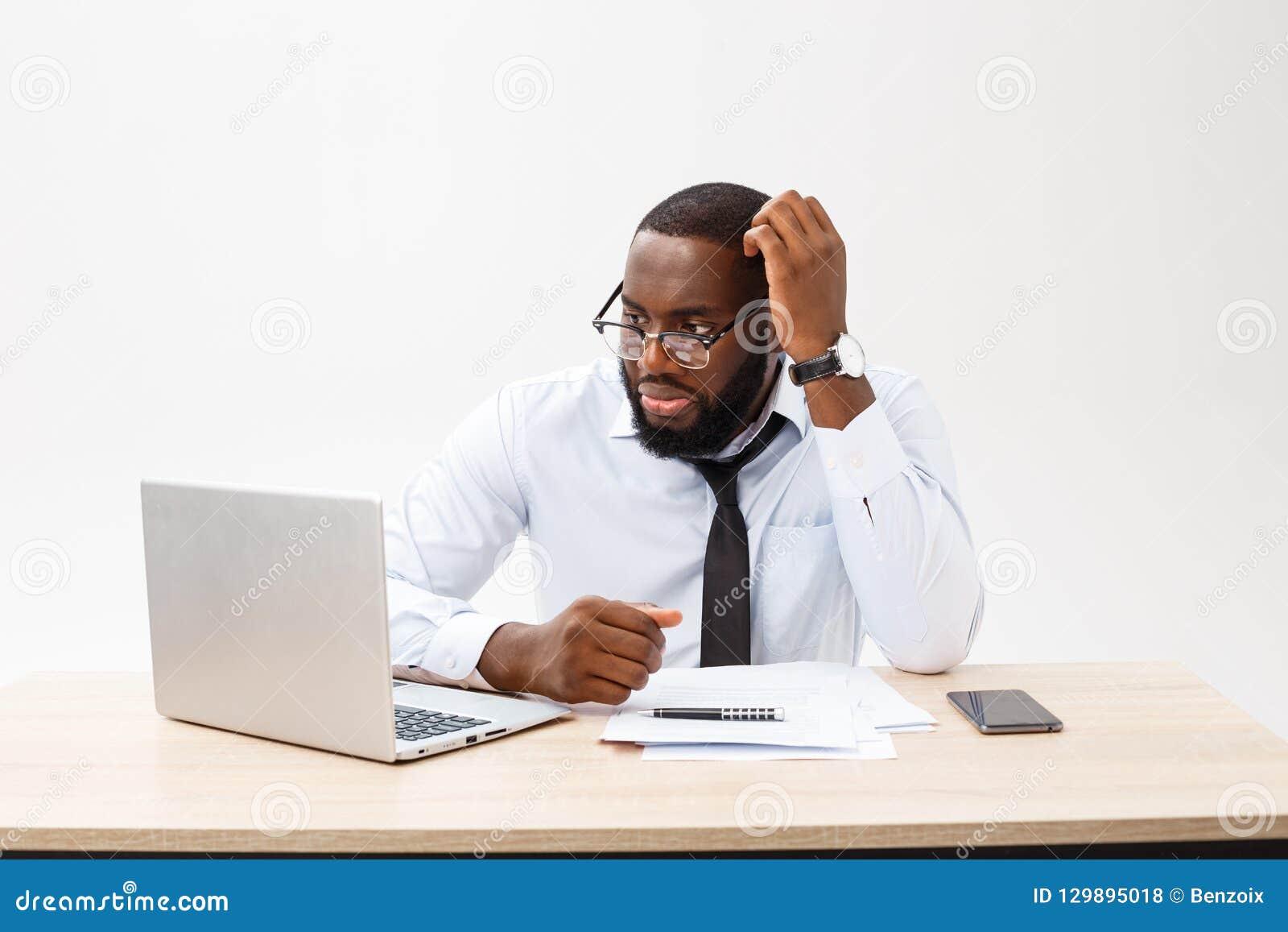 Affär och framgång Stilig lyckad afrikansk amerikanman som bär den formella dräkten, genom att använda bärbar datordatoren för av