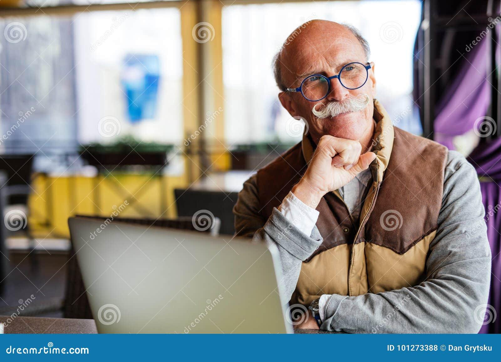Affär, teknologi och folkbegrepp - hög man med bärbar datordatoren på stadsgatakafét