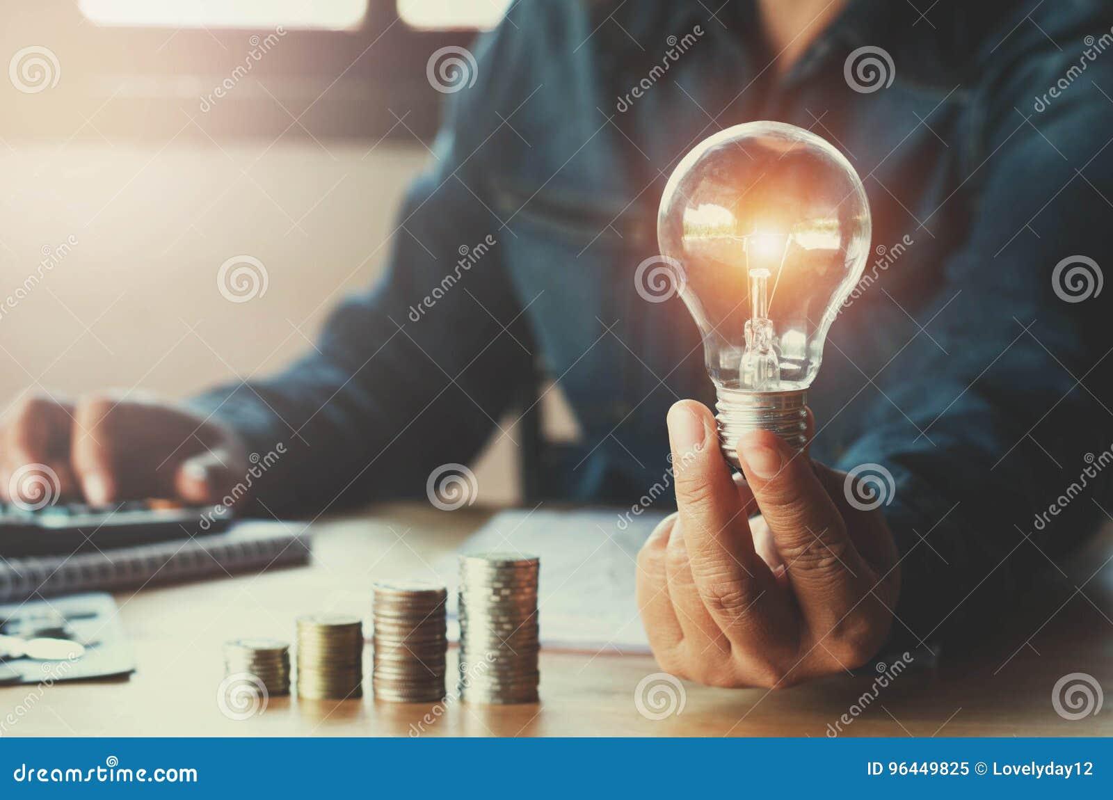 Affärsaccountin med sparande pengar med den hållande lightbulben för hand