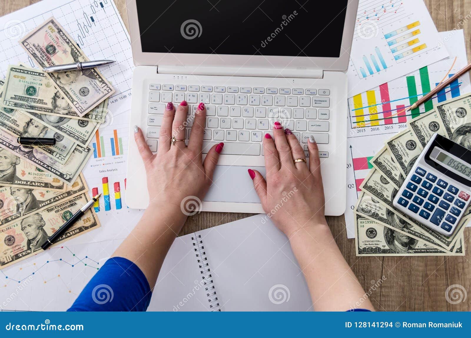 Affärsarbetaren rymmer US dollar i hand med bärbara datorn