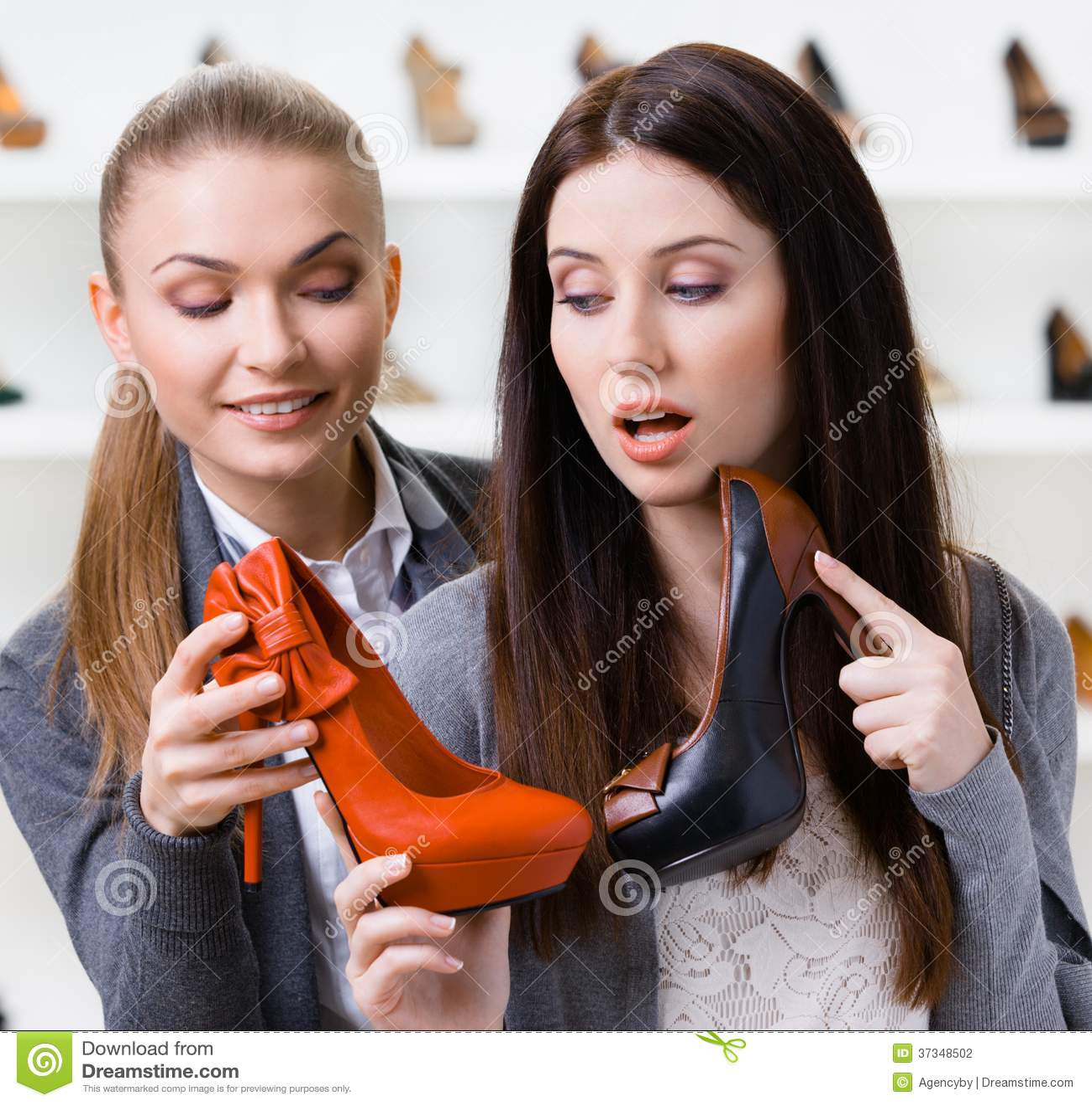 Affärsbiträdet erbjuder stilfulla skor för kunden