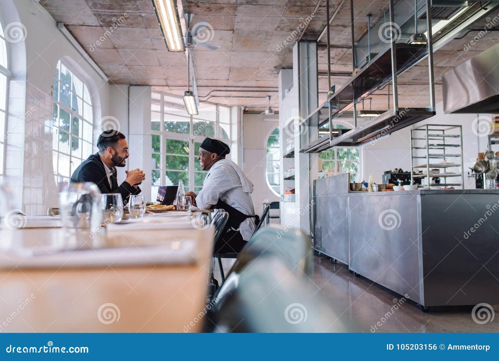 Affärschef och kock som talar i restaurang