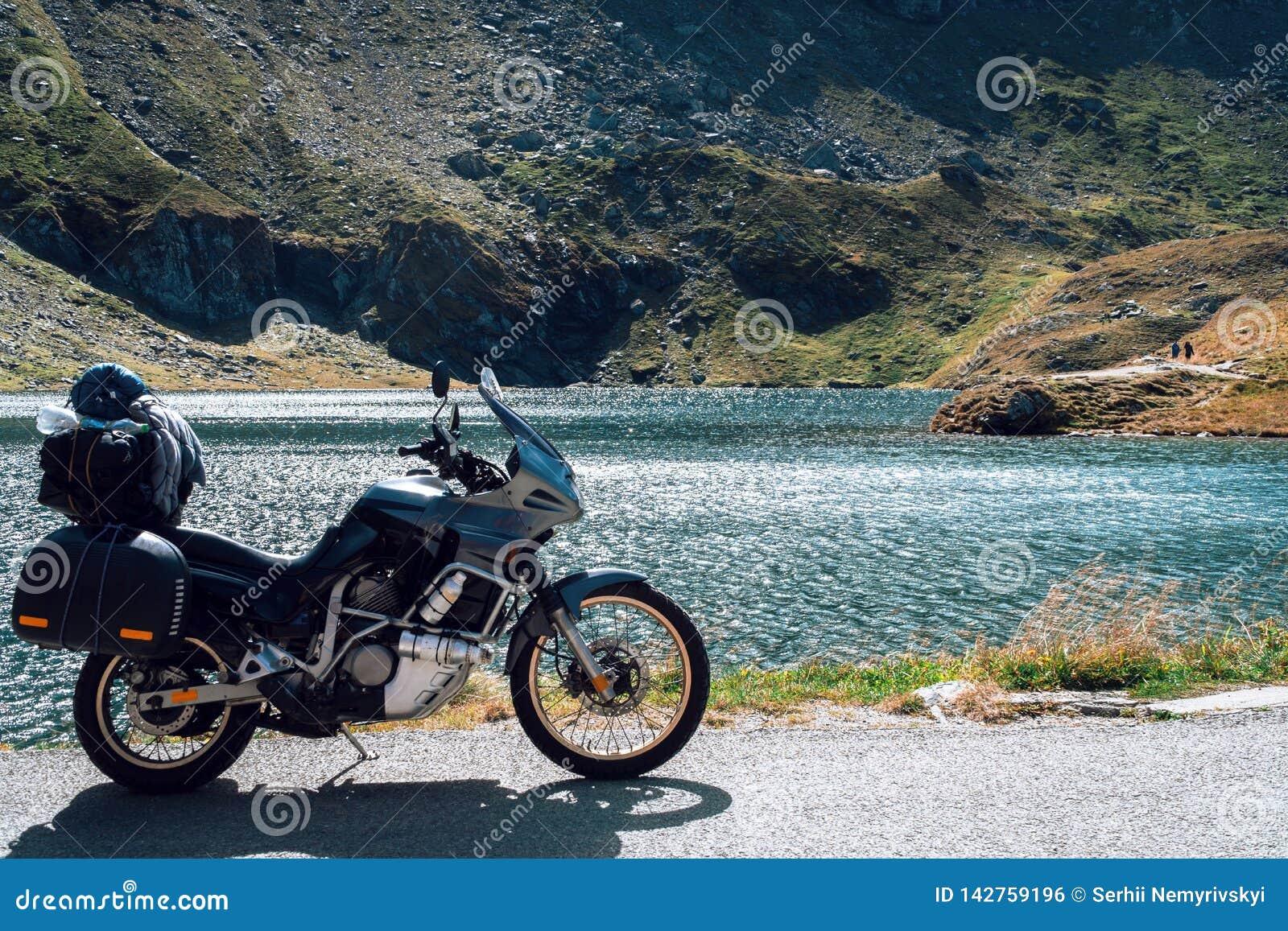 Affärsföretagmotorcykel i höstbergen av Rumänien Moto turism och motohandelsresandelivsstil, medan resa Europa Sjö