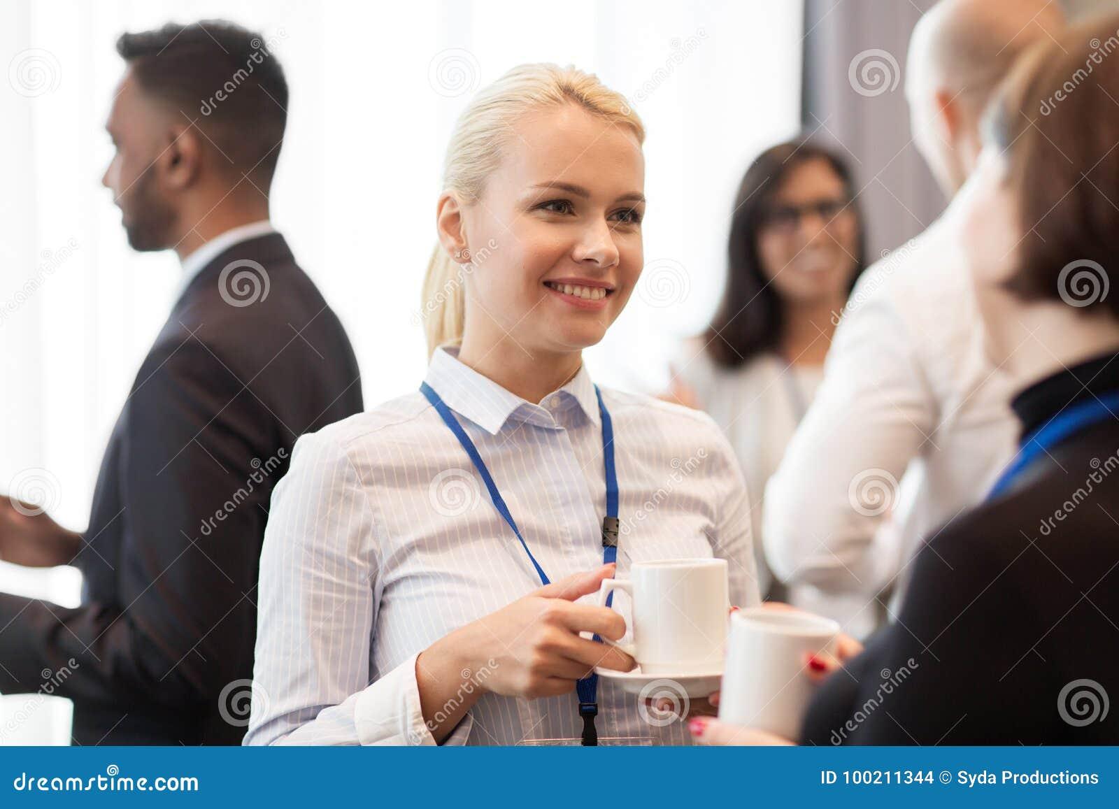 Affärsfolk med konferensemblem och kaffe