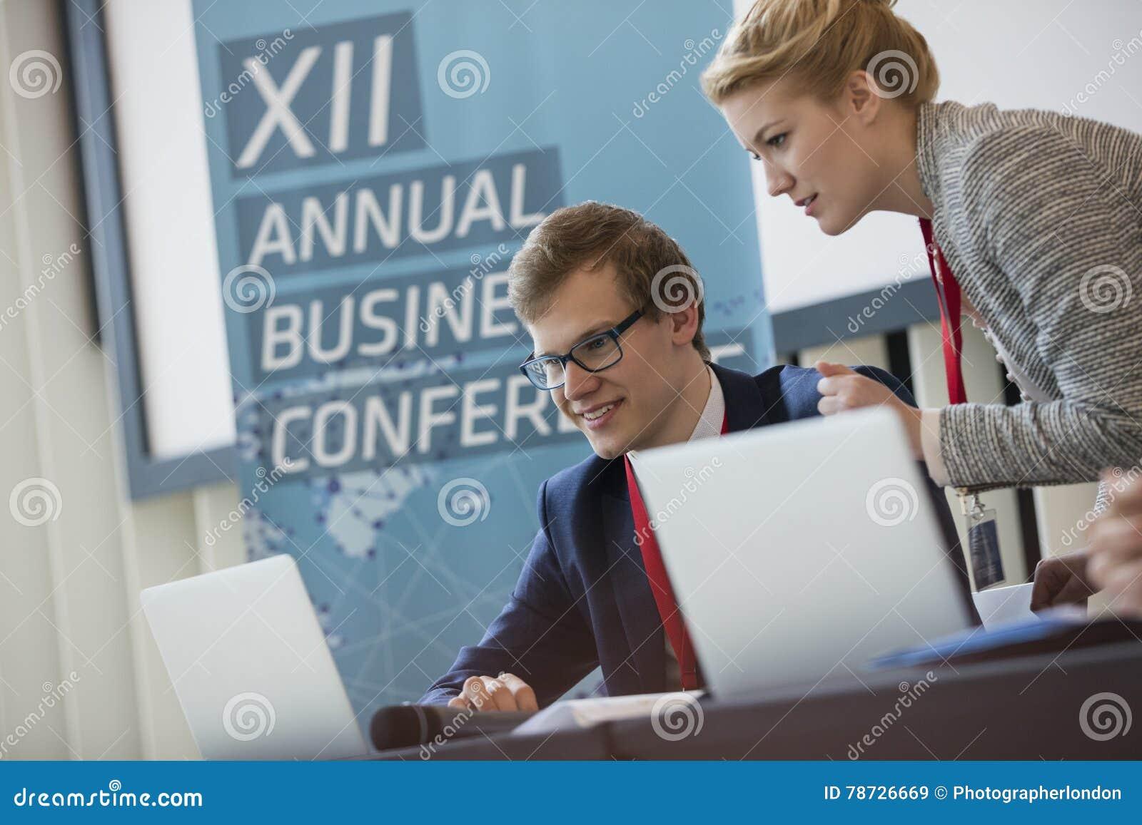 Affärsfolk som använder bärbara datorn i seminariumkorridor