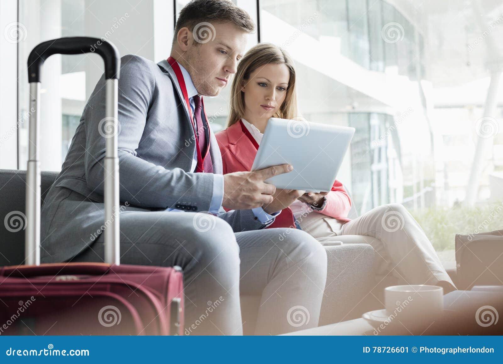 Affärsfolk som använder den digitala minnestavlan, medan sitta på lobbyen i konventcentrum