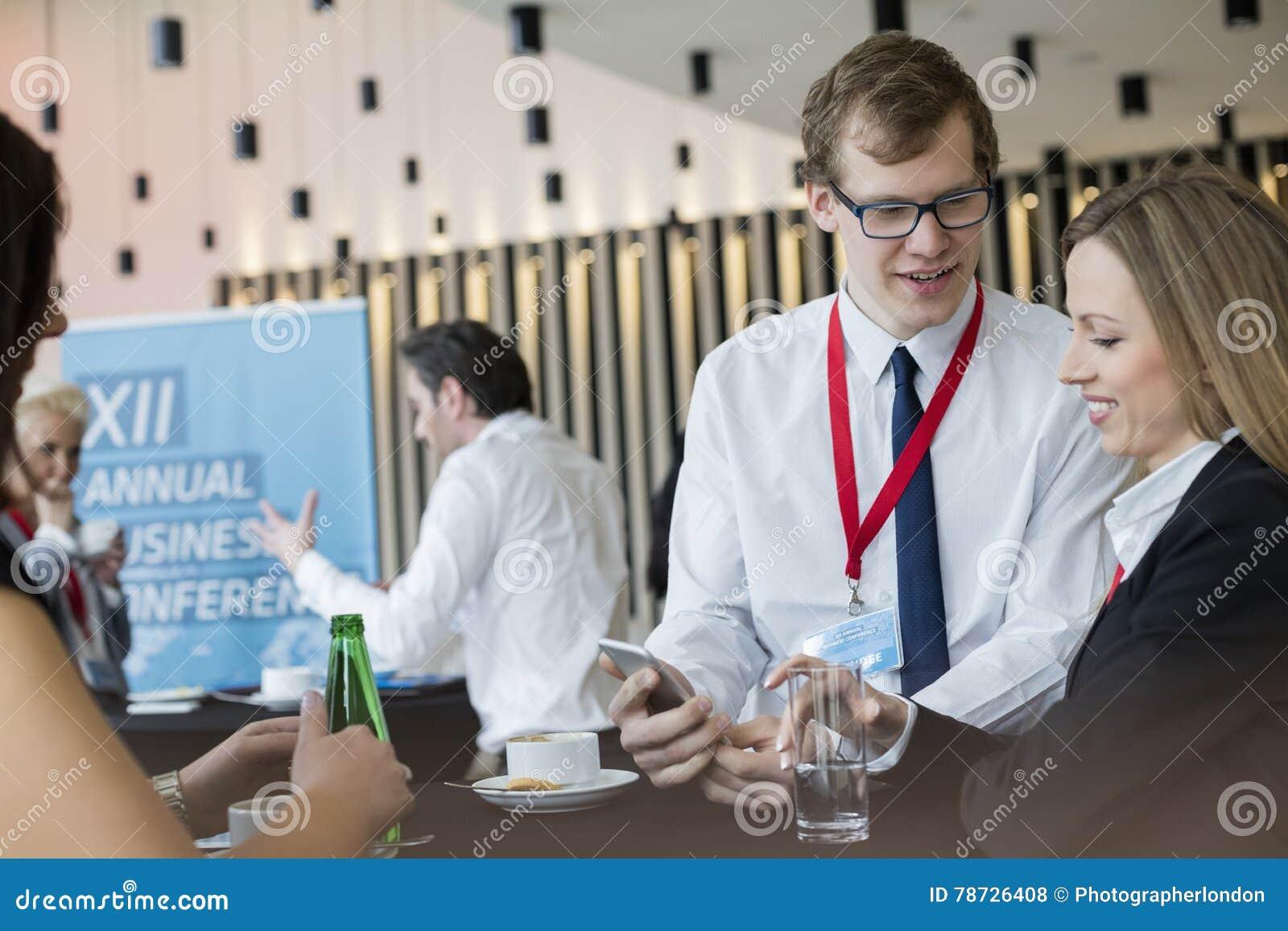 Affärsfolk som använder den smarta telefonen under kaffeavbrott på konventcentret