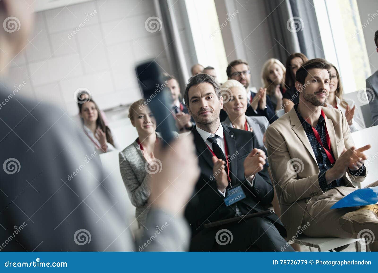 Affärsfolk som applåderar för offentlig högtalare under seminarium