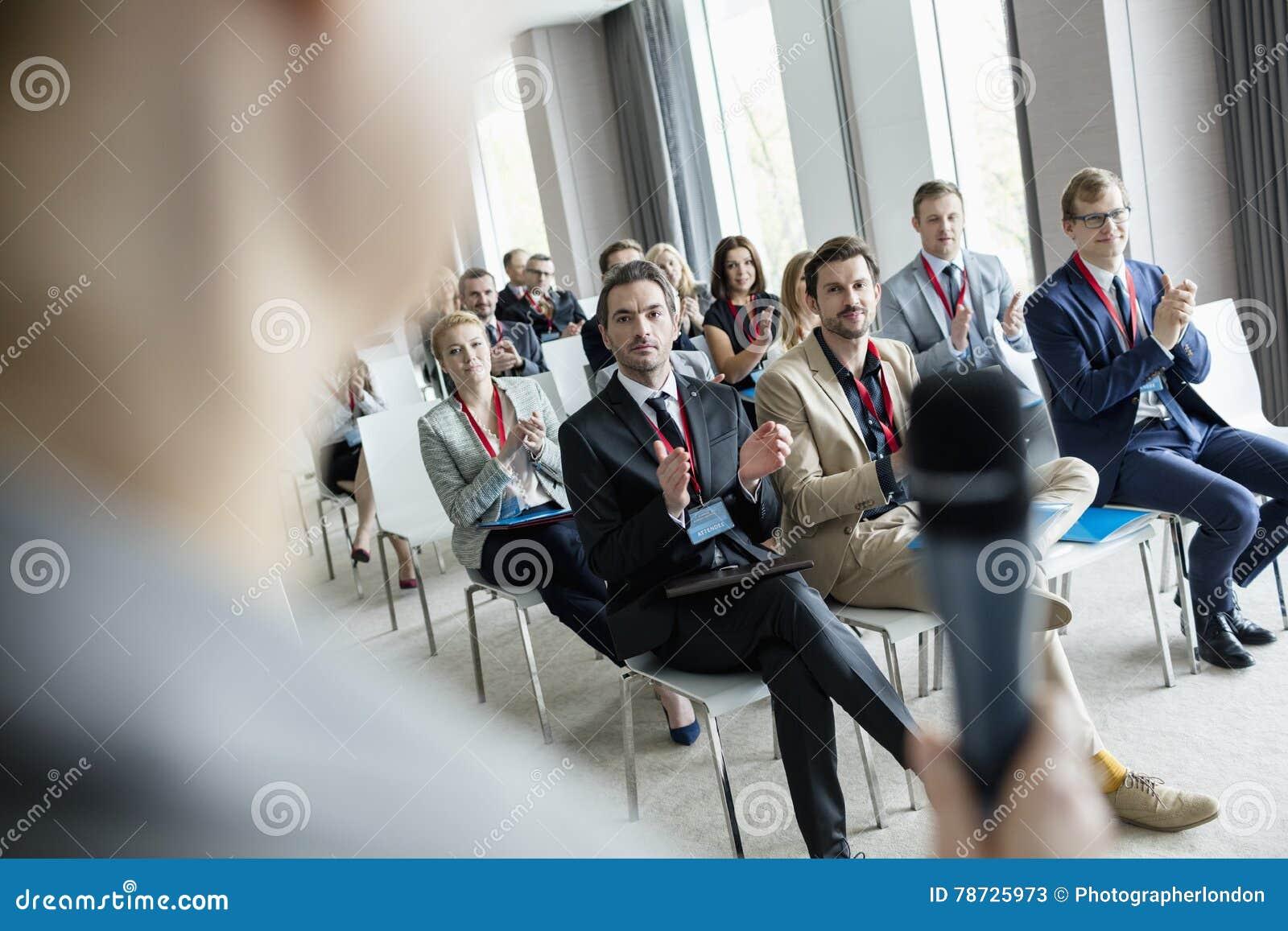 Affärsfolk som applåderar för offentlig högtalare under seminarium på konventcentret