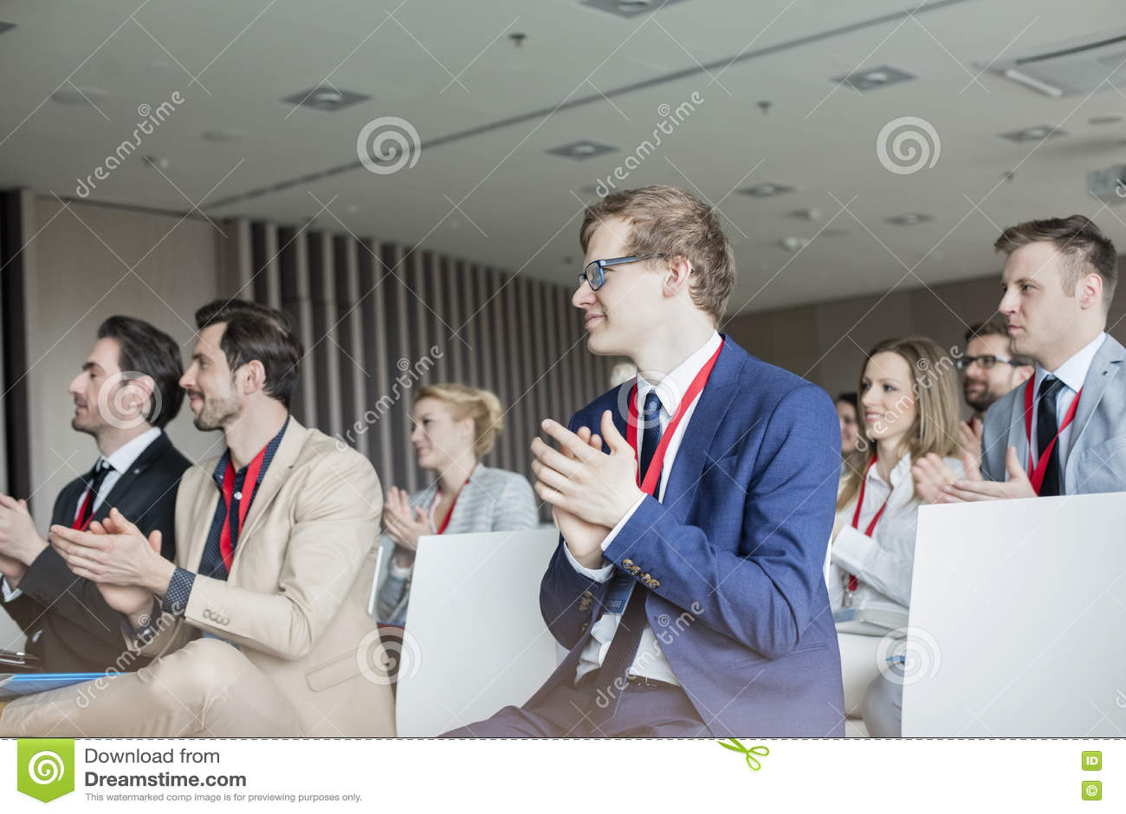 Affärsfolk som applåderar under seminarium