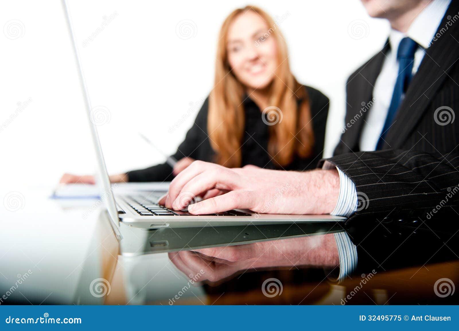 Affärsfolk som arbetar och skriver på en bärbar dator