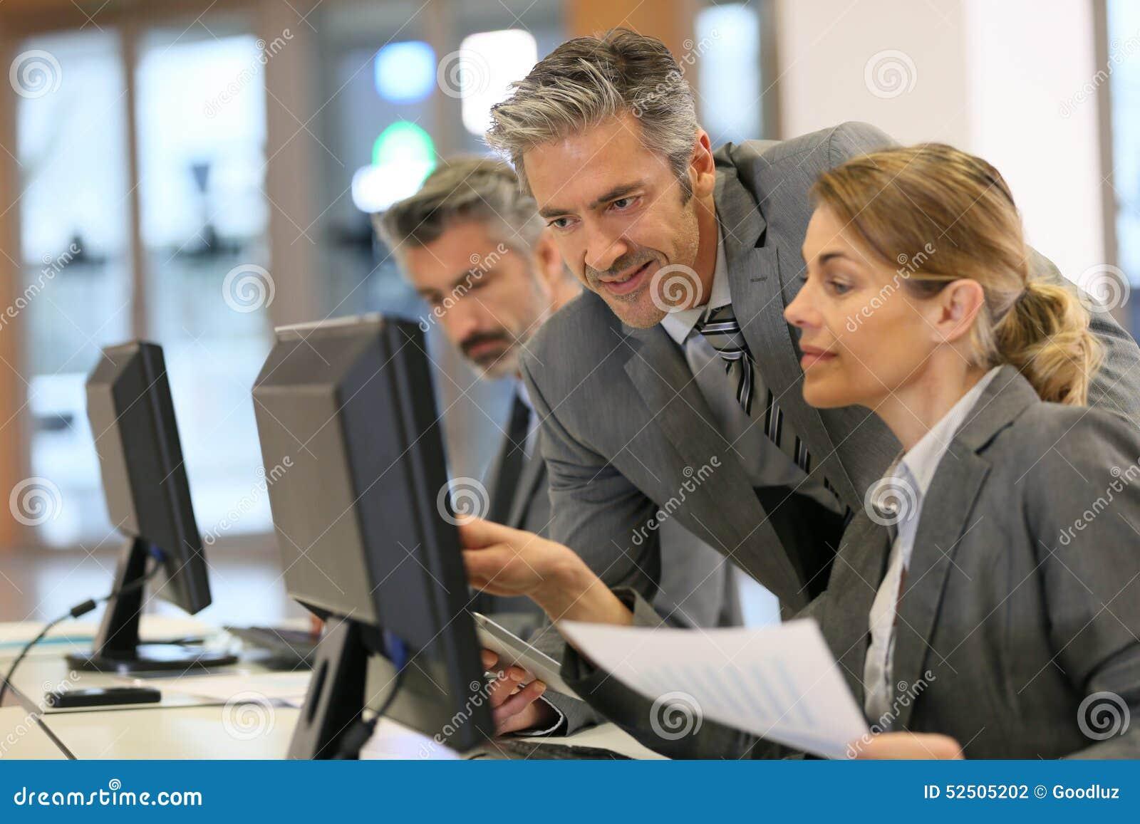 Affärsfolk som arbetar på kontoret på den skrivbords- datoren